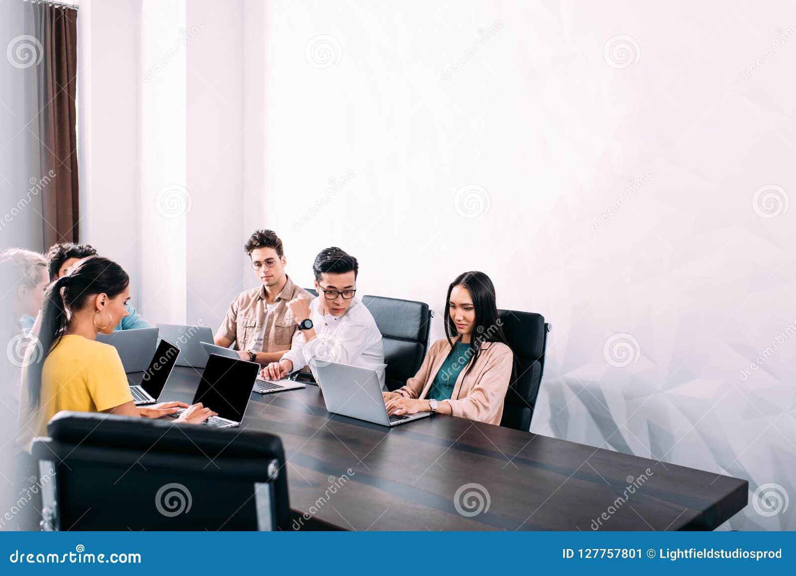 Mångkulturella affärspartners som har möte på tabellen med bärbara datorer i modernt