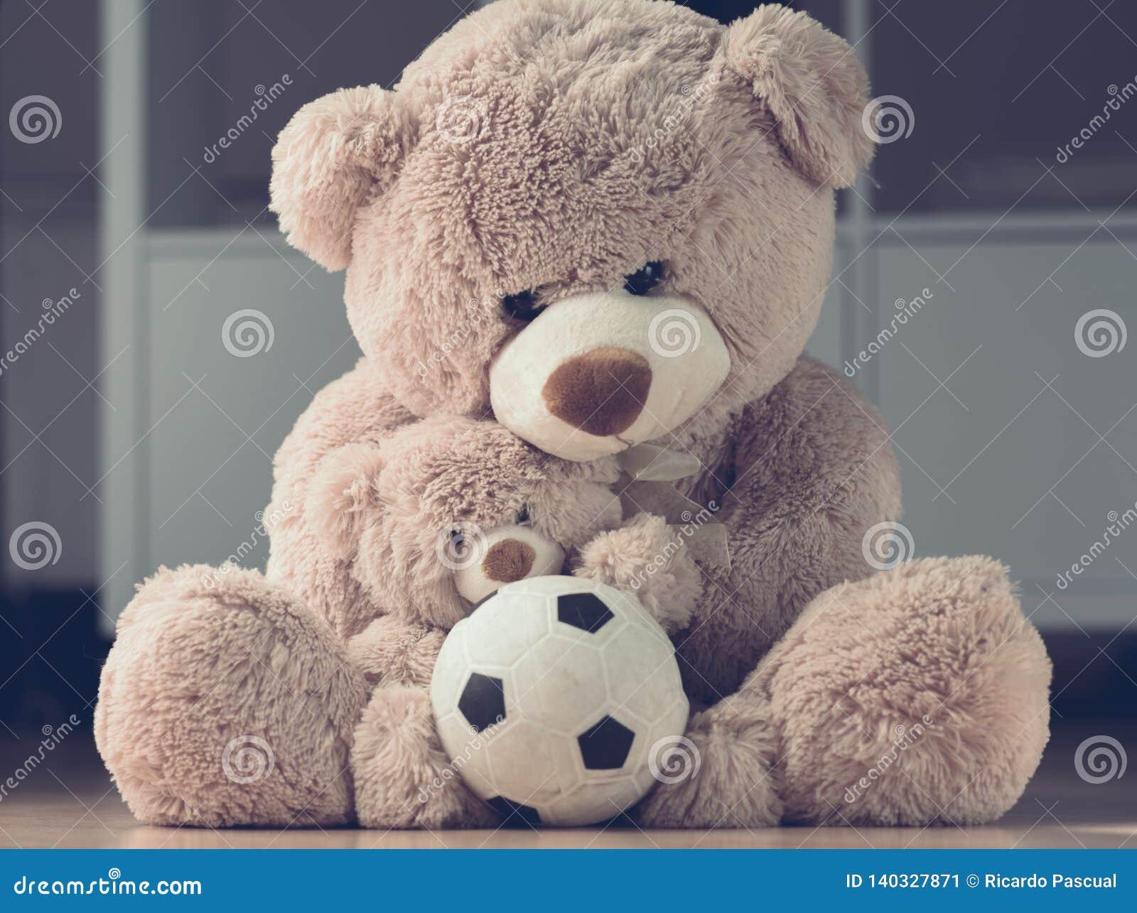 Mère étreignant son ours de nounours de fils avec la boule
