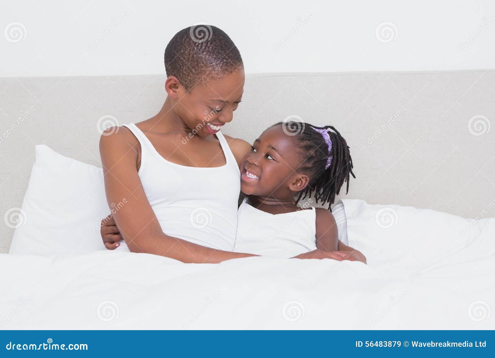 Mère assez belle avec sa fille dans son lit