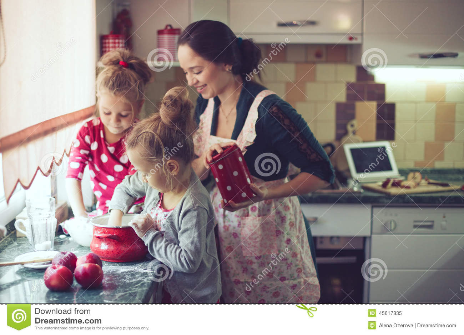 Mère avec des enfants à la cuisine