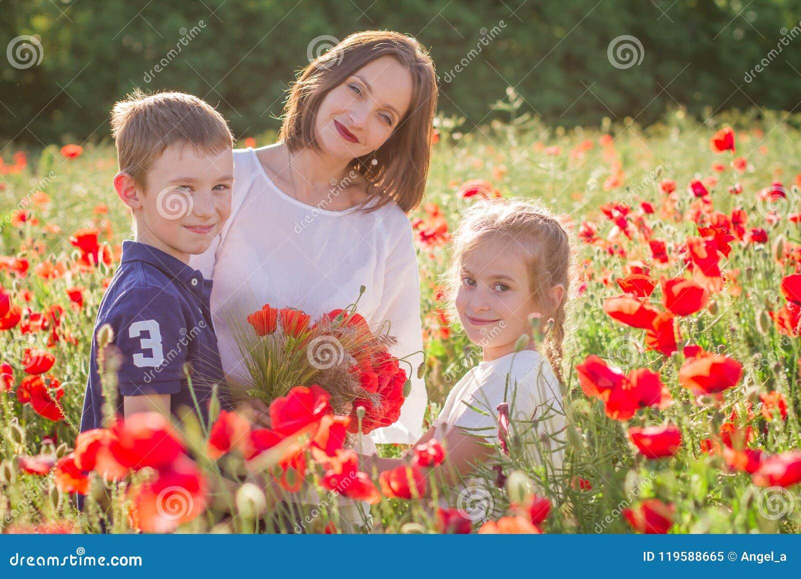 Mère avec deux enfants parmi le champ rouge de pavot