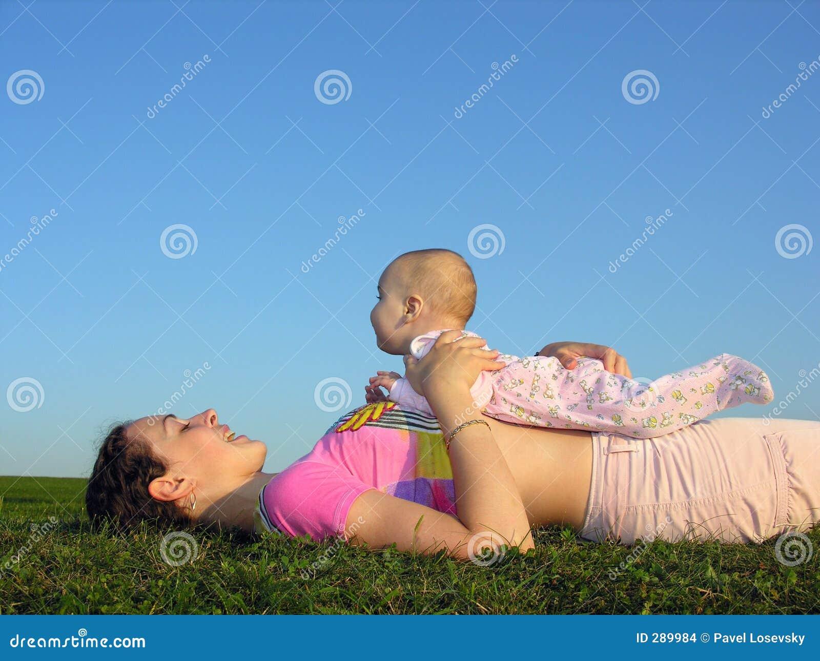 Mère avec la chéri sur le mensonge de coucher du soleil