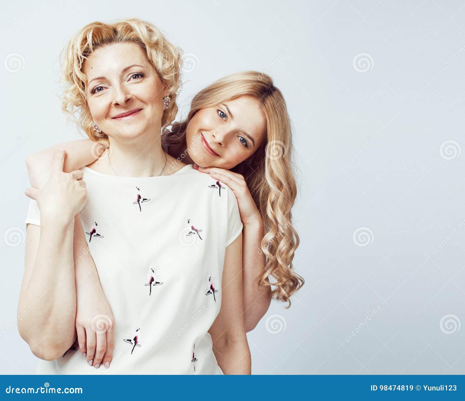 Mère avec la fille posant ensemble le sourire heureux d isolement sur le fond blanc avec le copyspace, concept de personnes de mo