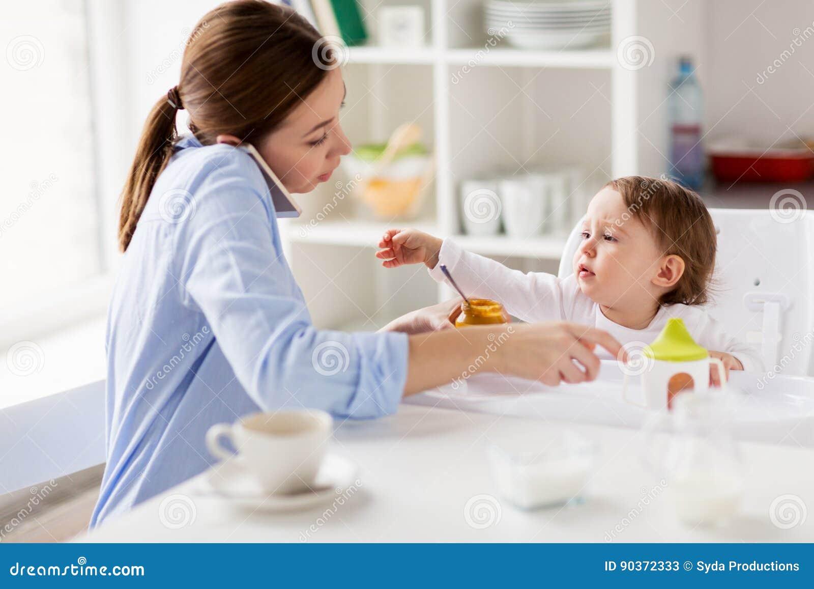 Mère avec le bébé de alimentation de smartphone à la maison