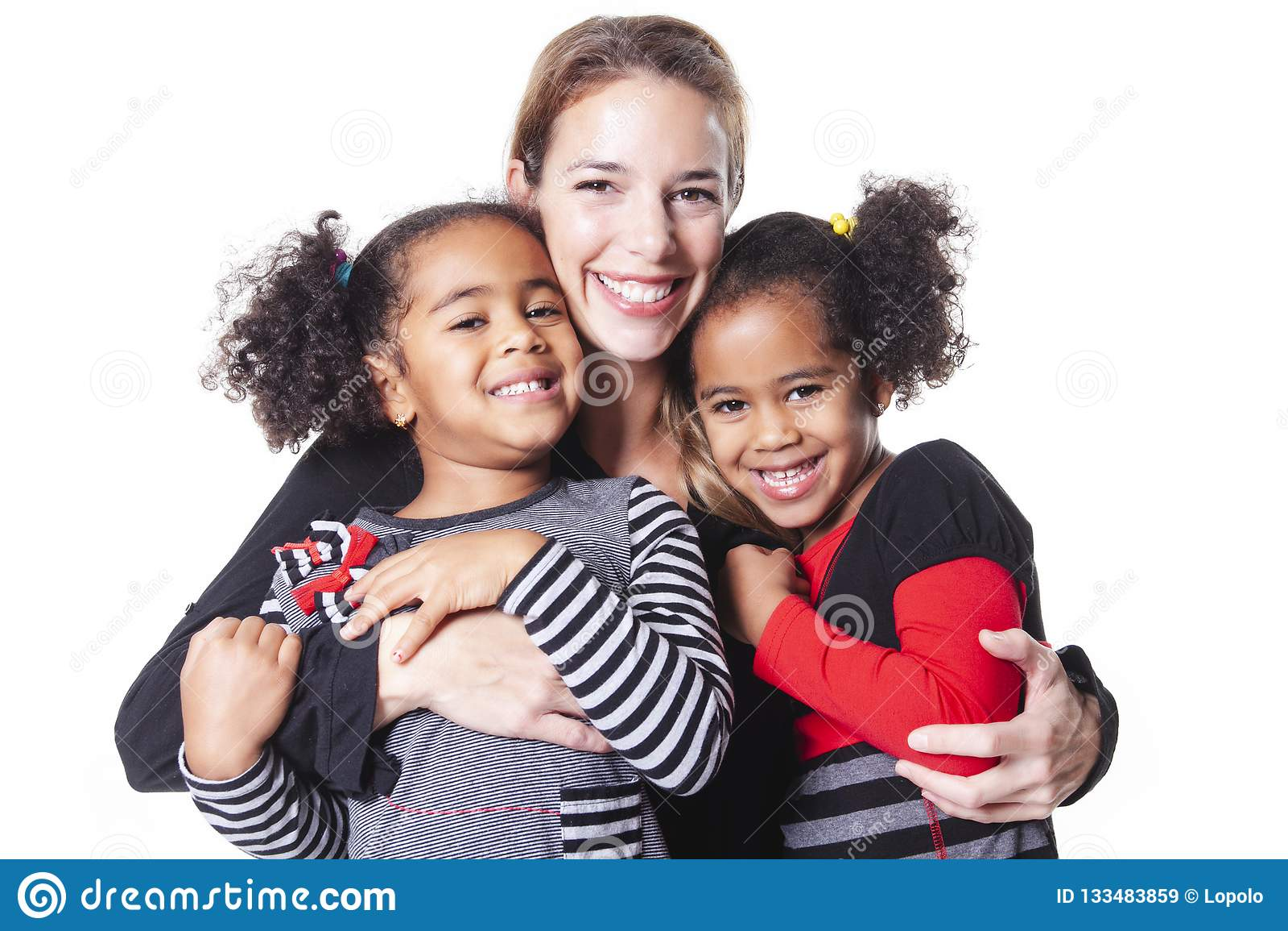 Mère blanche avec la famille noire d enfant posant sur un studio blanc de fond