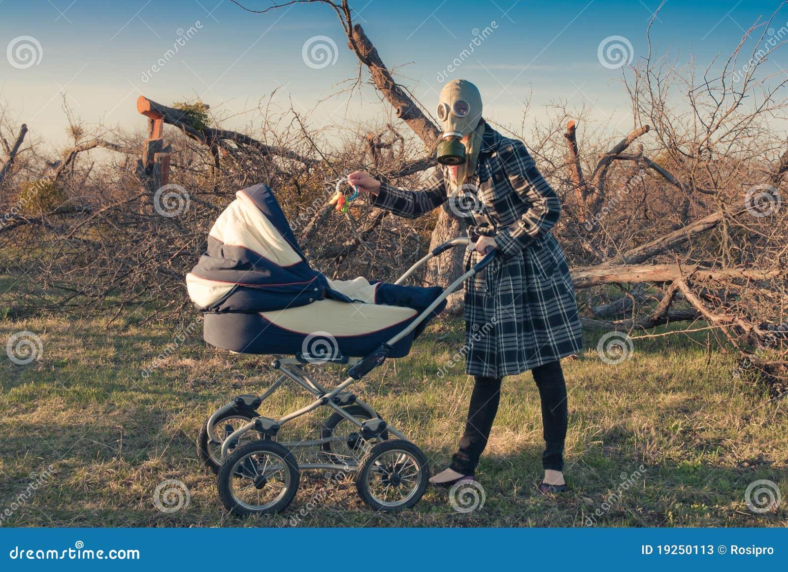 Mère dans le masque de gaz avec la poussette de chéri