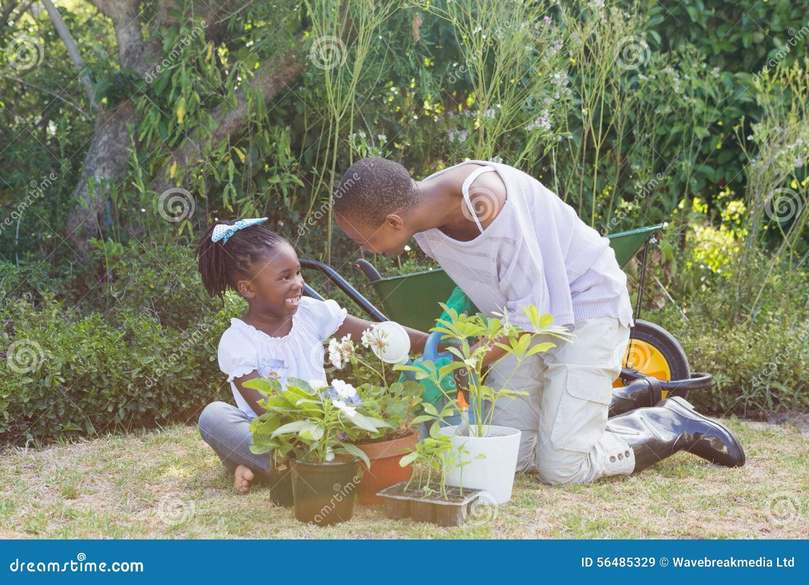 Mère de sourire heureuse faisant du jardinage avec sa fille