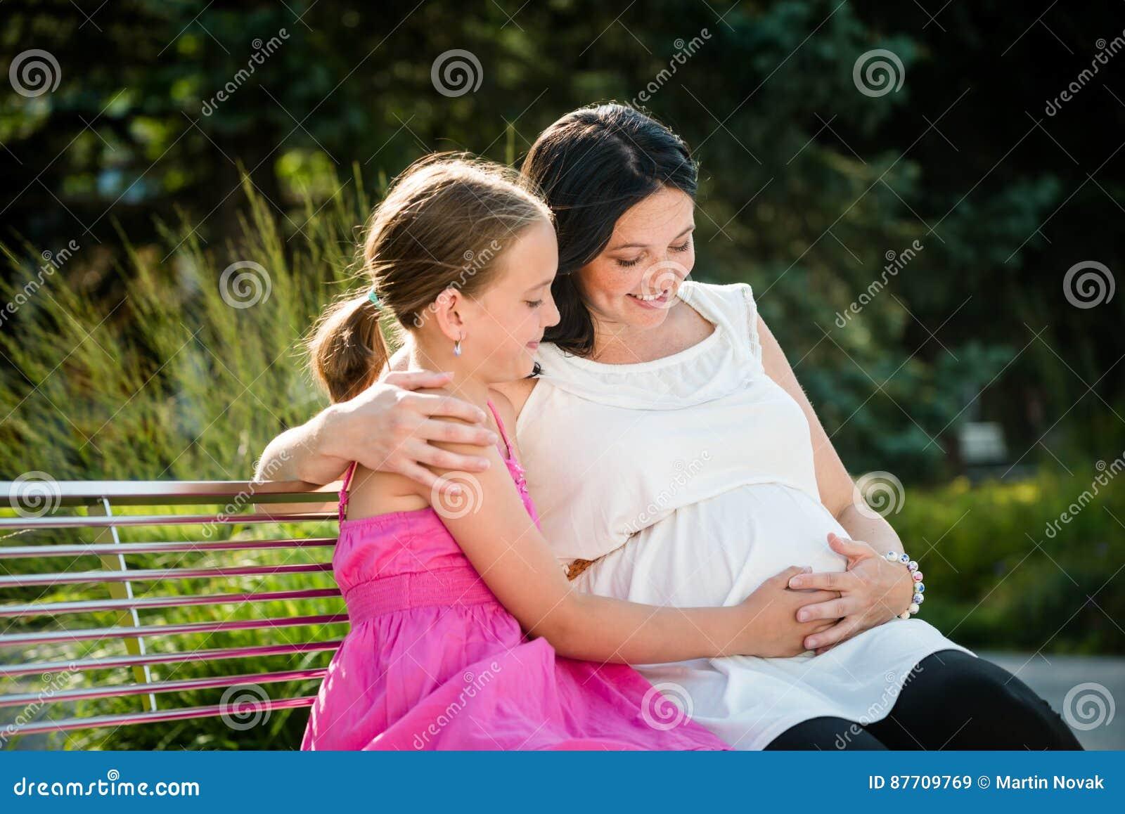 Mère enceinte embrassant sa fille mignonne
