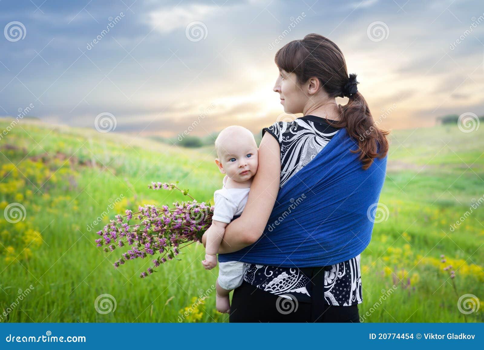 Mère et bébé dans l élingue sur le pré vert