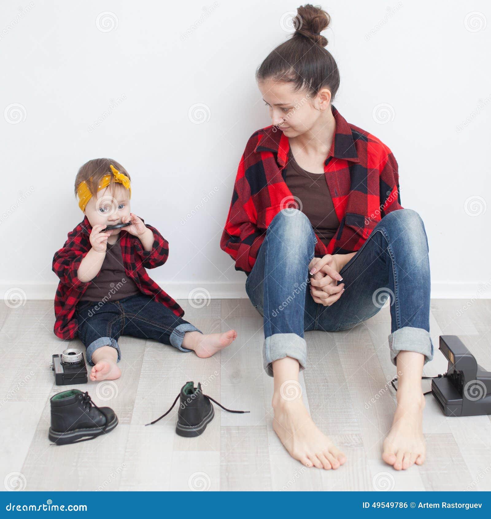 Mère et bébé dans les chemises à carreaux et des jeans