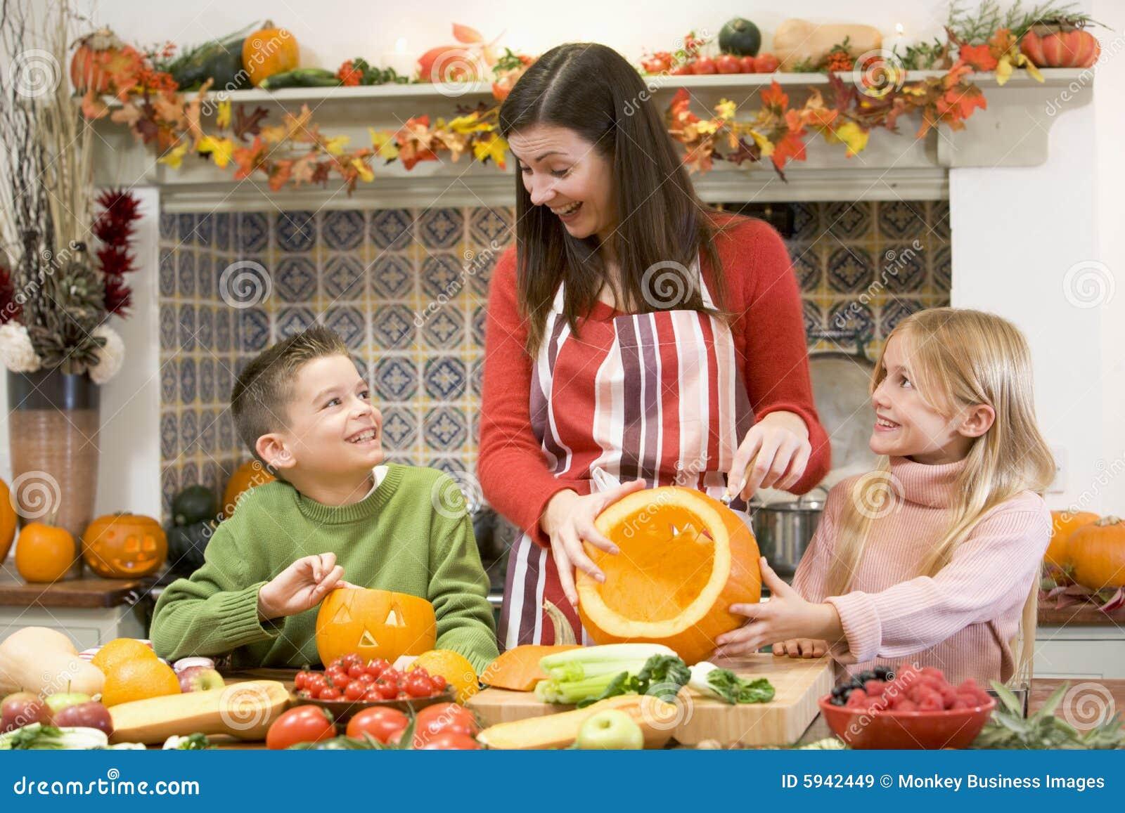 Mère et deux enfants découpant des potirons