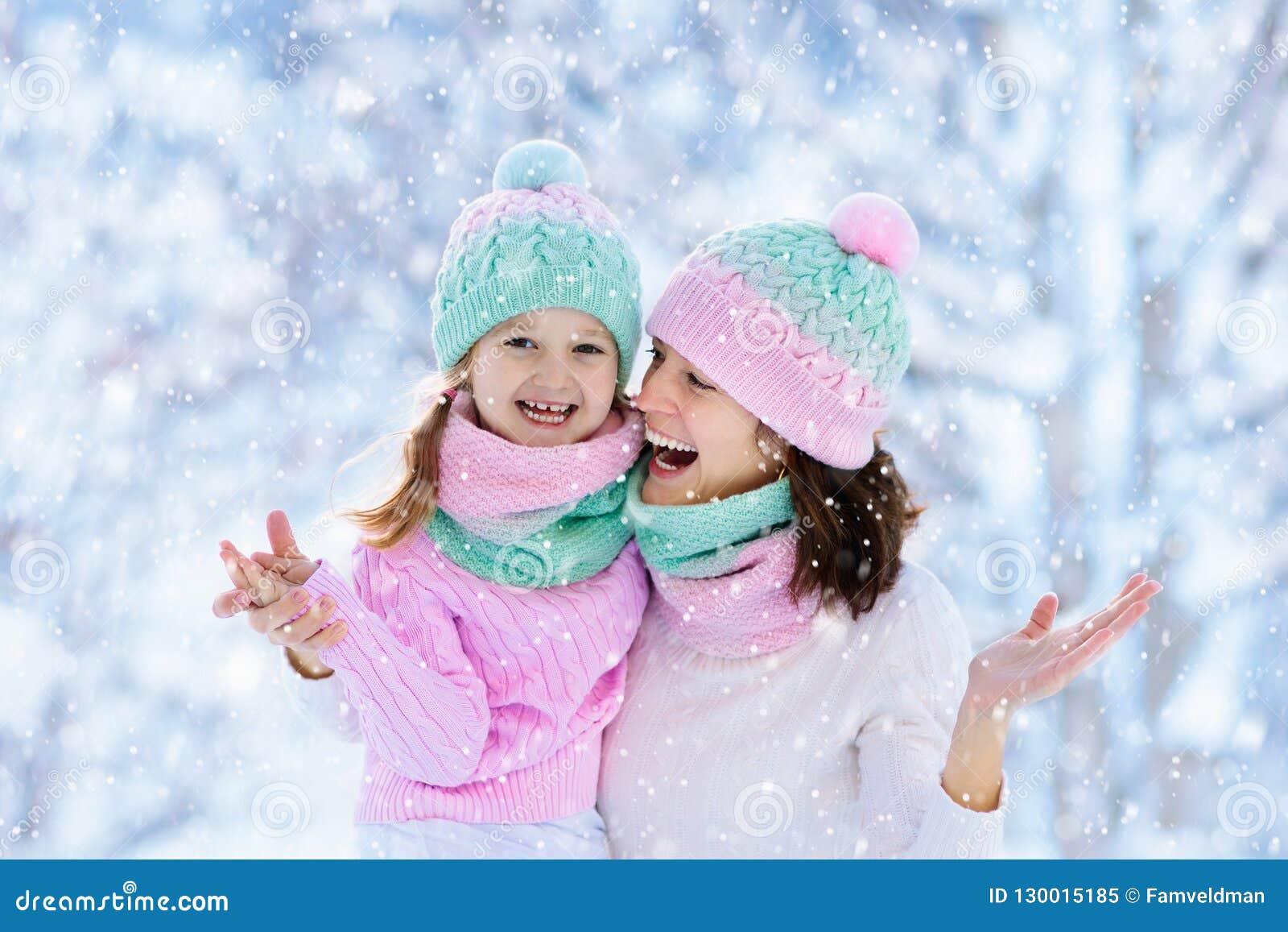Mère et enfant dans des chapeaux tricotés d hiver dans la neige
