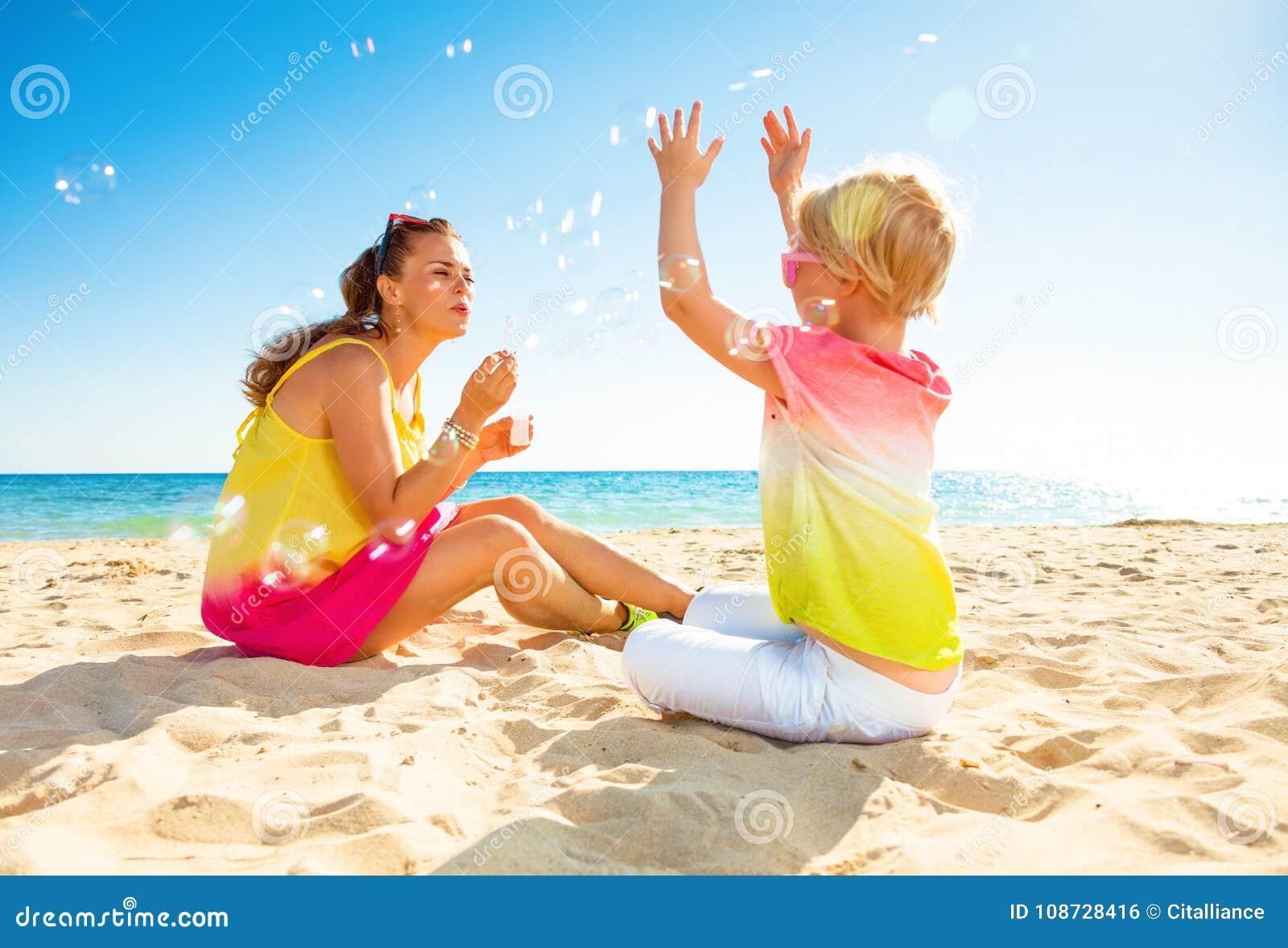 Mère et fille à la mode de sourire sur les bulles de soufflement de littoral