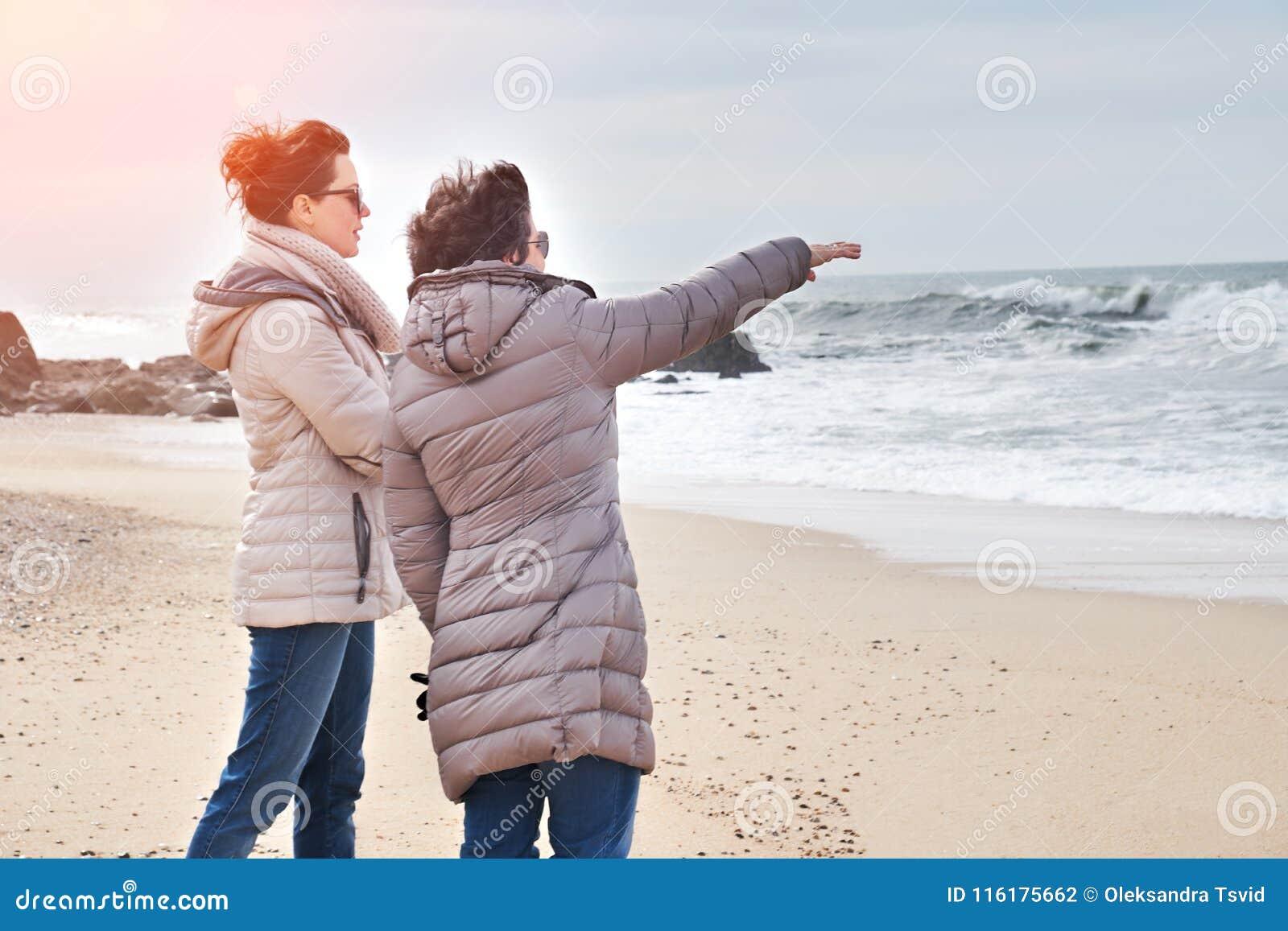 Mère et fille appréciant le coucher du soleil sur la plage