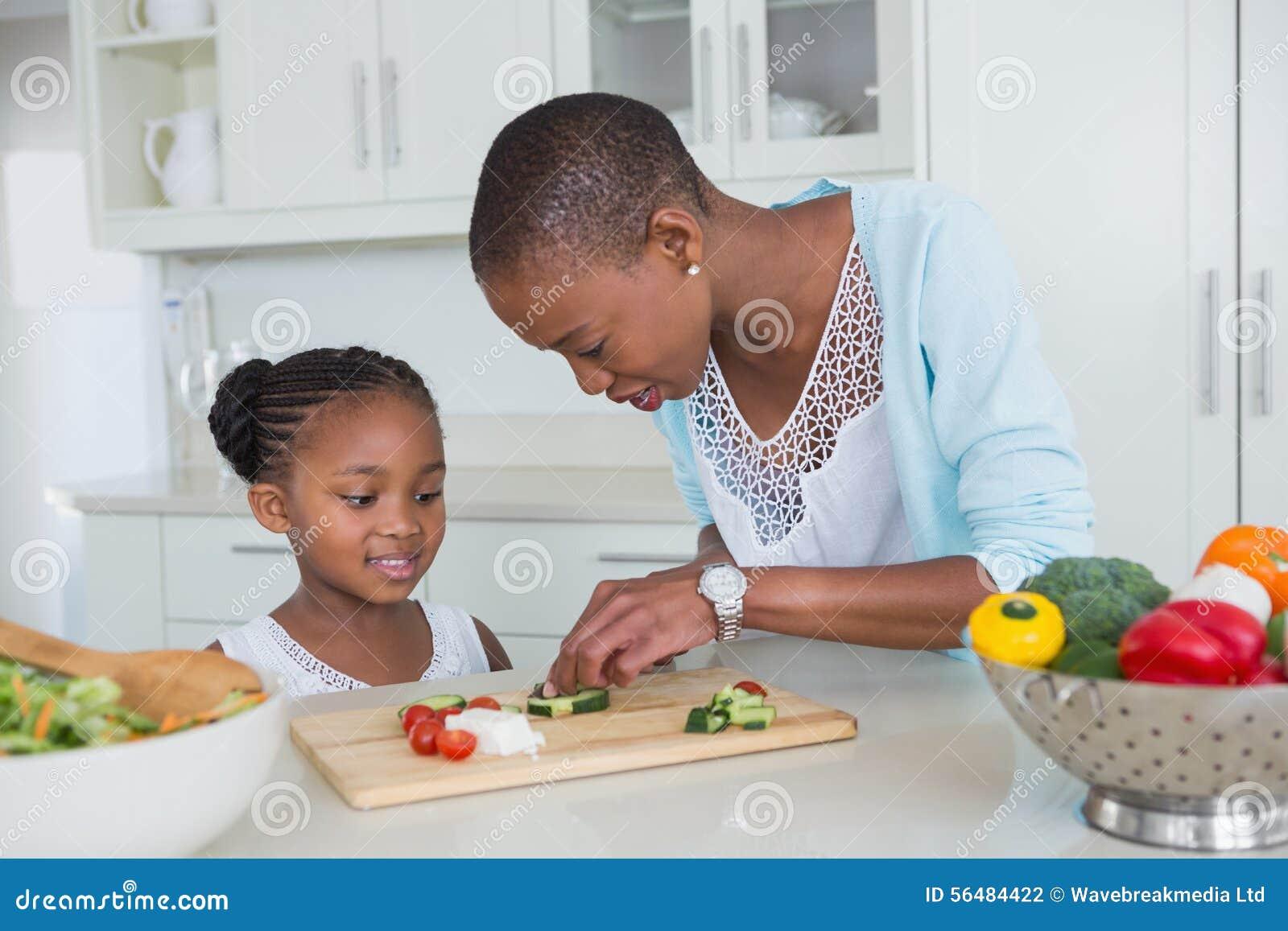 Mère et fille de portrait faisant une salade ensemble