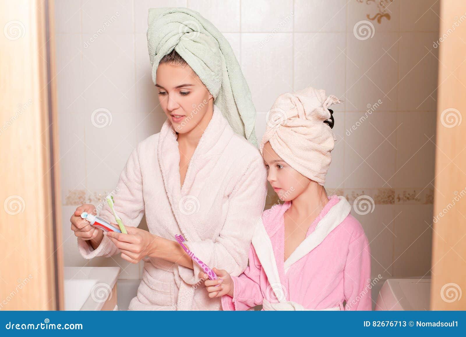 Mère et fille de sourire se brossant les dents