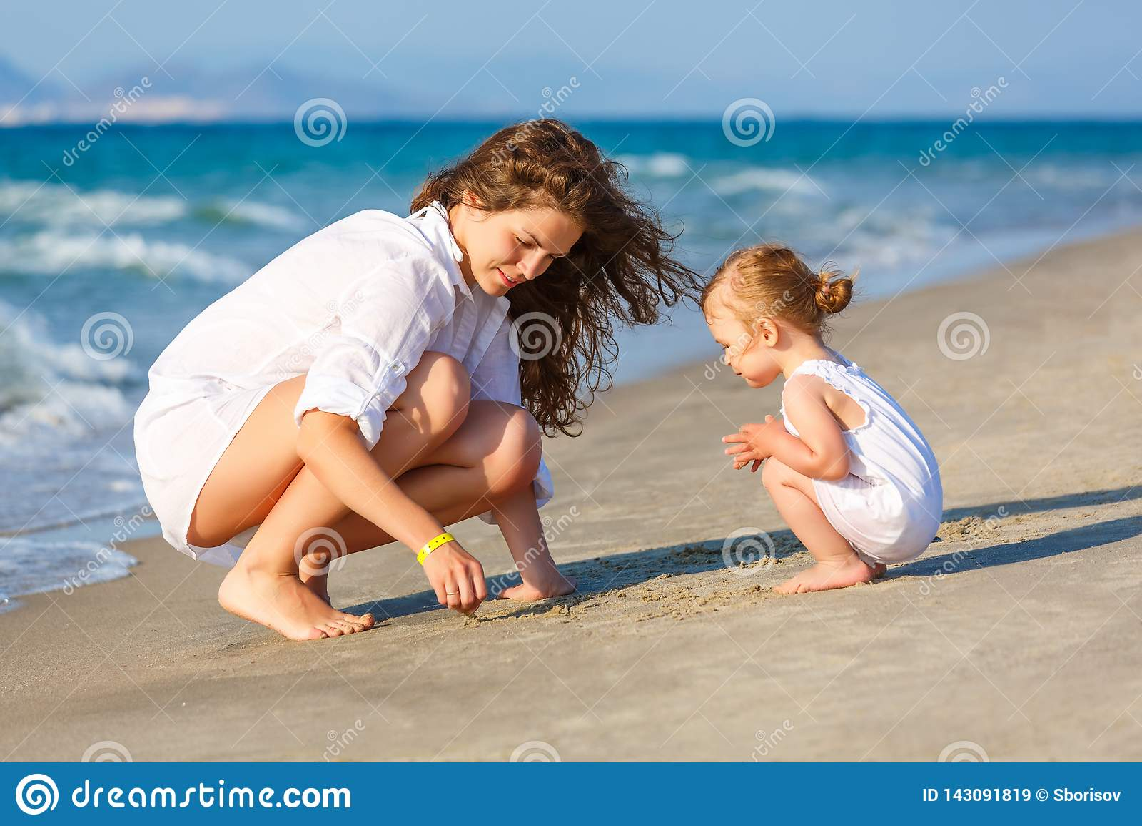 Mère et fille jouant sur la plage de mer en Grèce