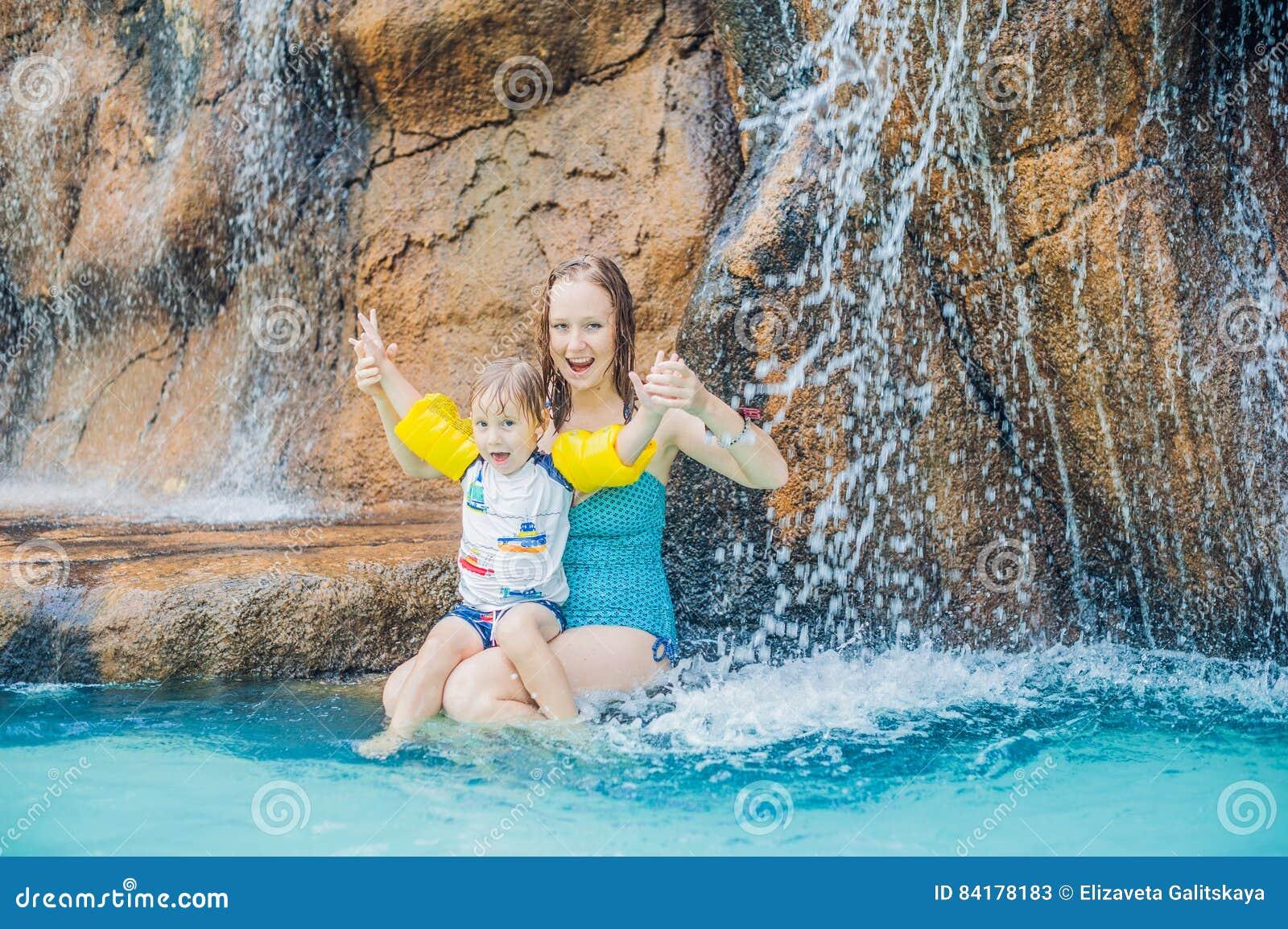 Mère et fils détendant sous une cascade dans l aquapark