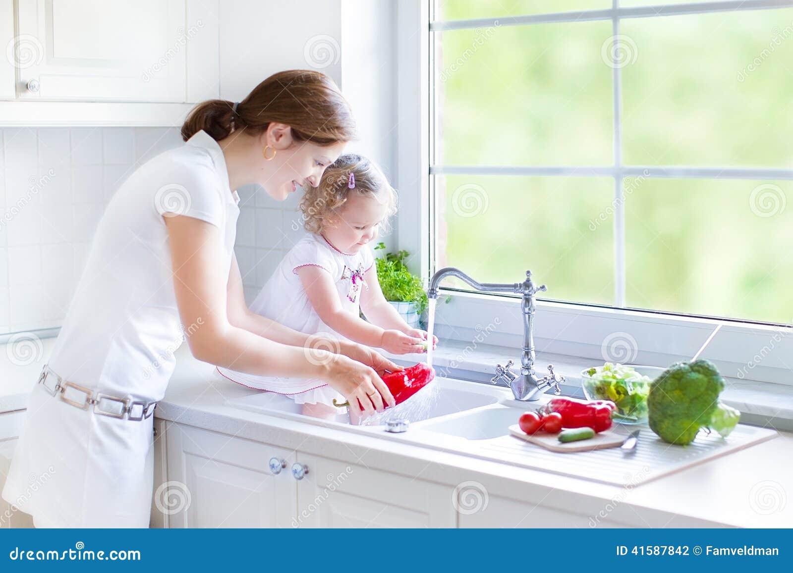 Mère et ses légumes de lavage de fille d enfant en bas âge