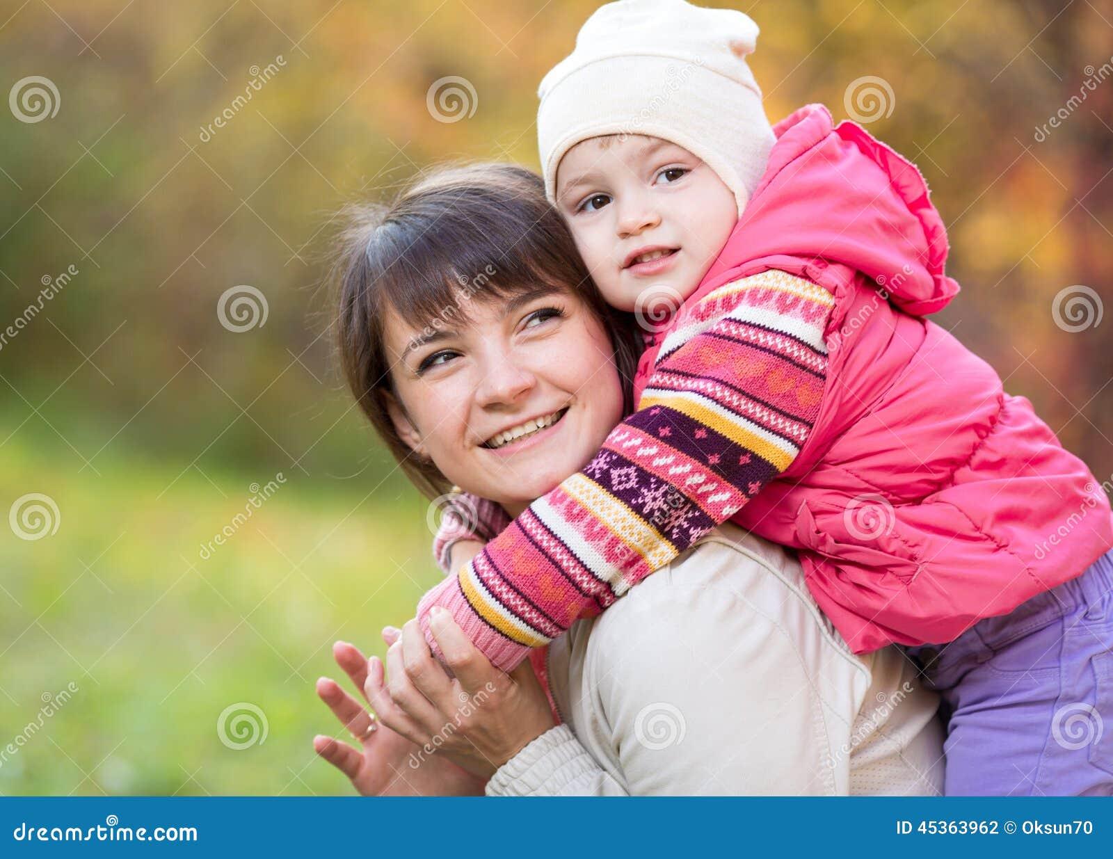 Mère heureuse avec la fille d enfant extérieure en parc d automne
