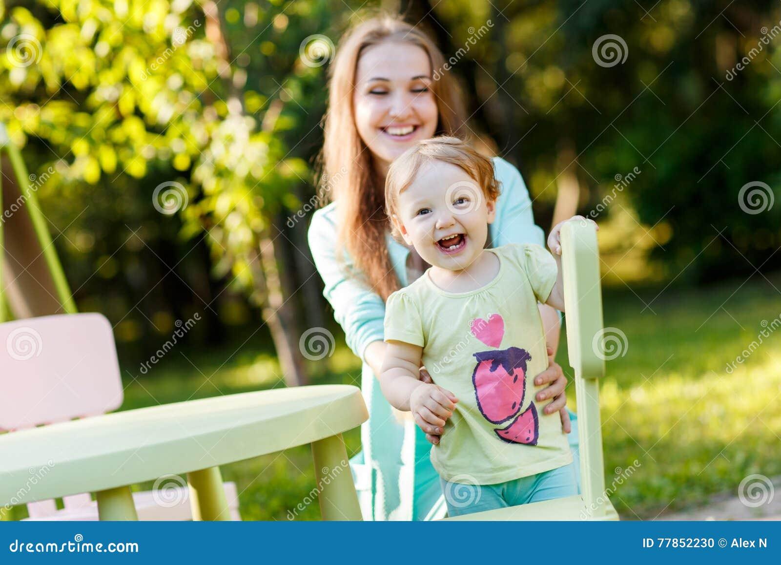Mère heureuse avec la fille s asseyant sur le children& x27 ; chaise de s