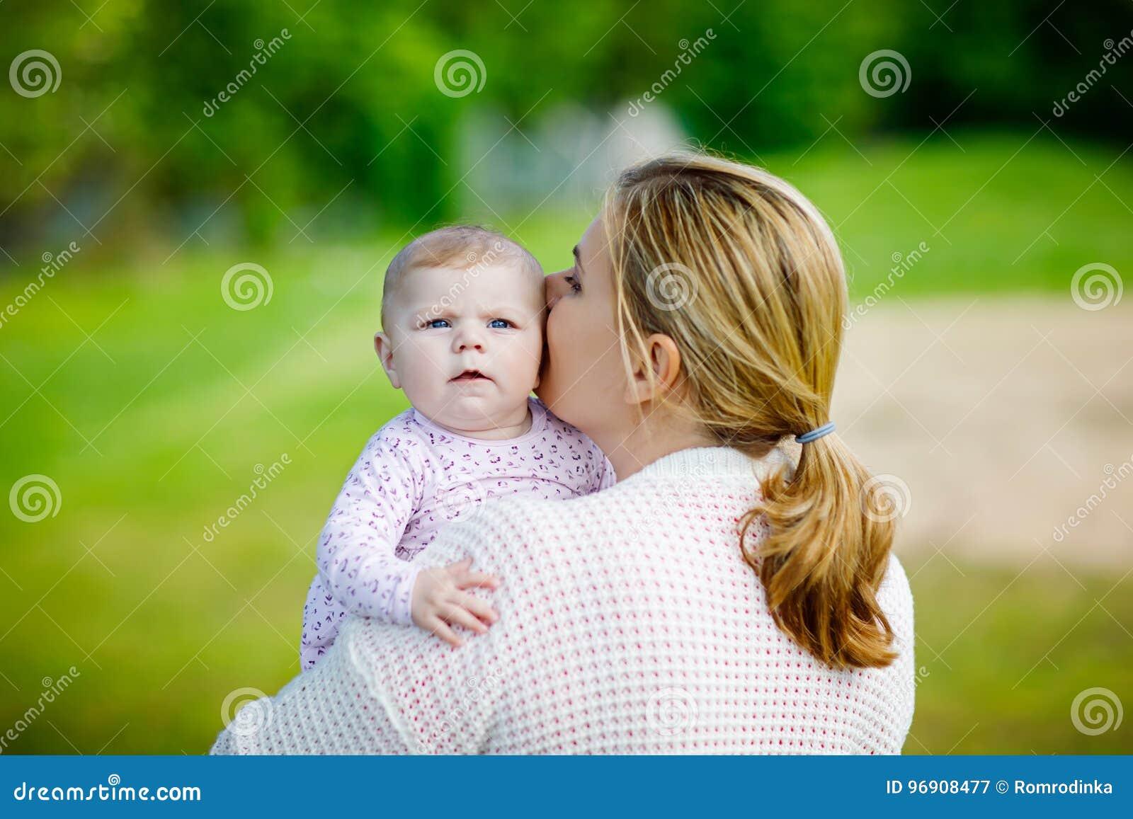 Mère heureuse ayant l amusement avec la fille nouveau-née de bébé dehors