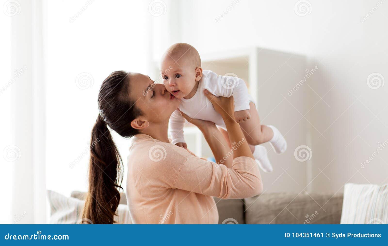 Mère heureuse embrassant le petit bébé garçon à la maison