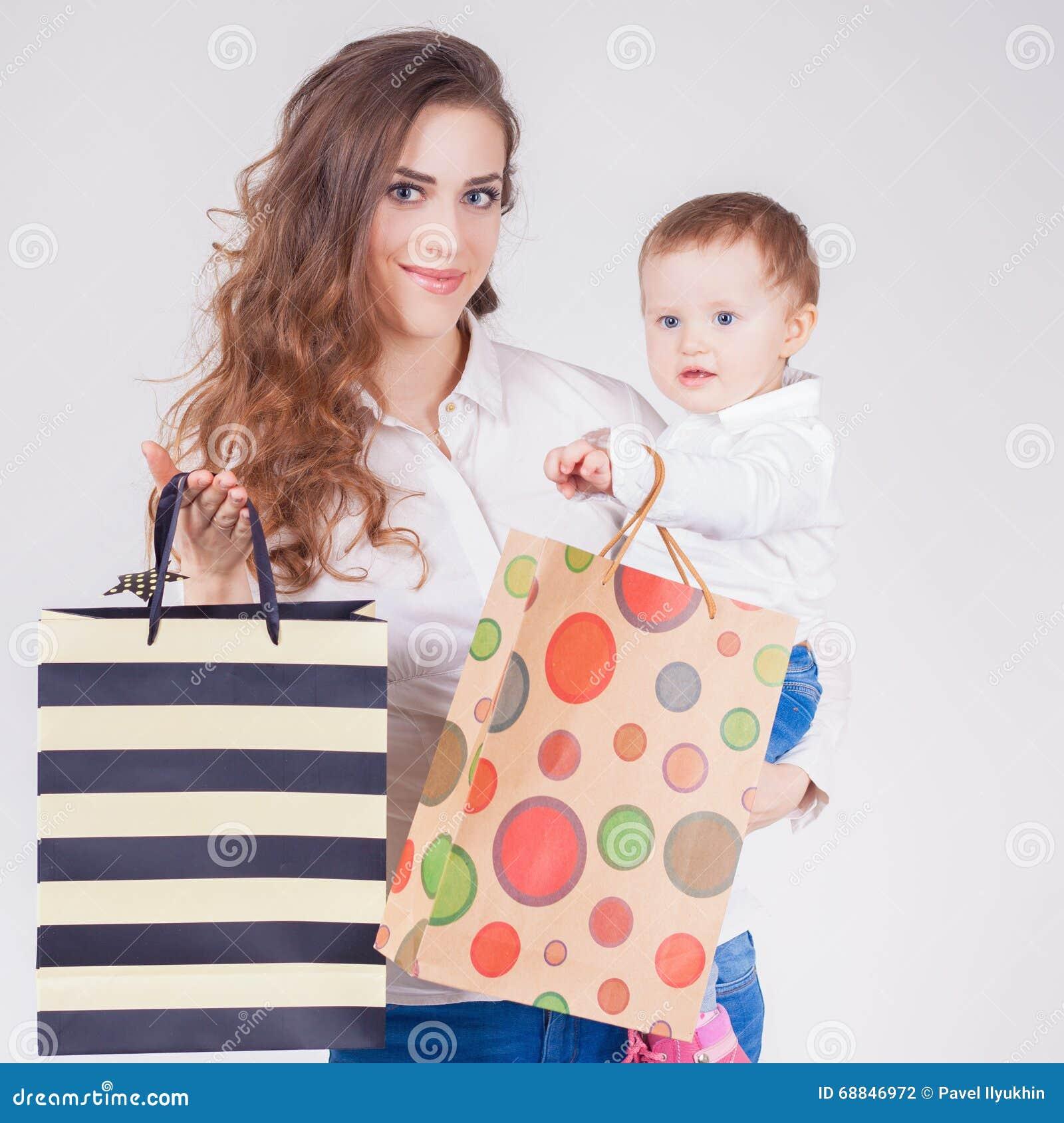 Mère heureuse et bébé drôle tenant des sacs avec des achats