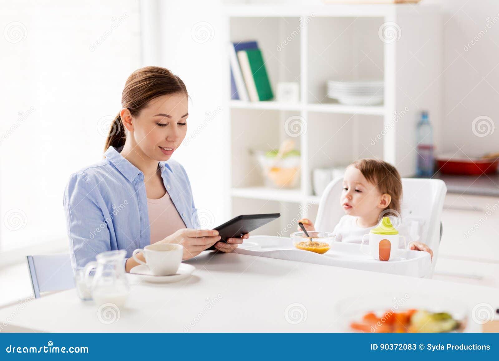 Mère heureuse et bébé prenant le petit déjeuner à la maison