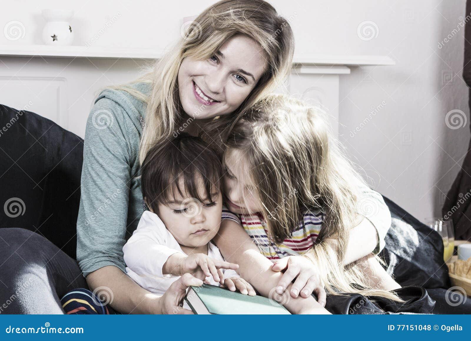 Mère lisant aux enfants dans le lit