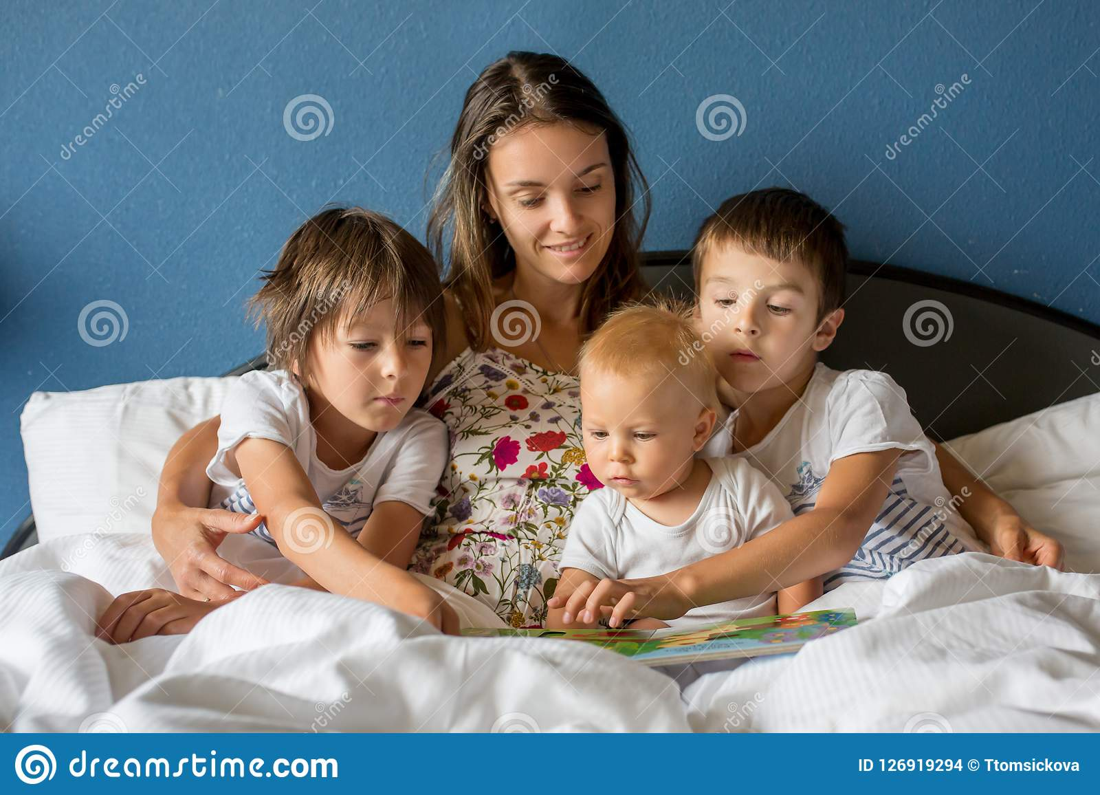 Mère, lisant un livre à ses enfants pendant le matin dans le lit