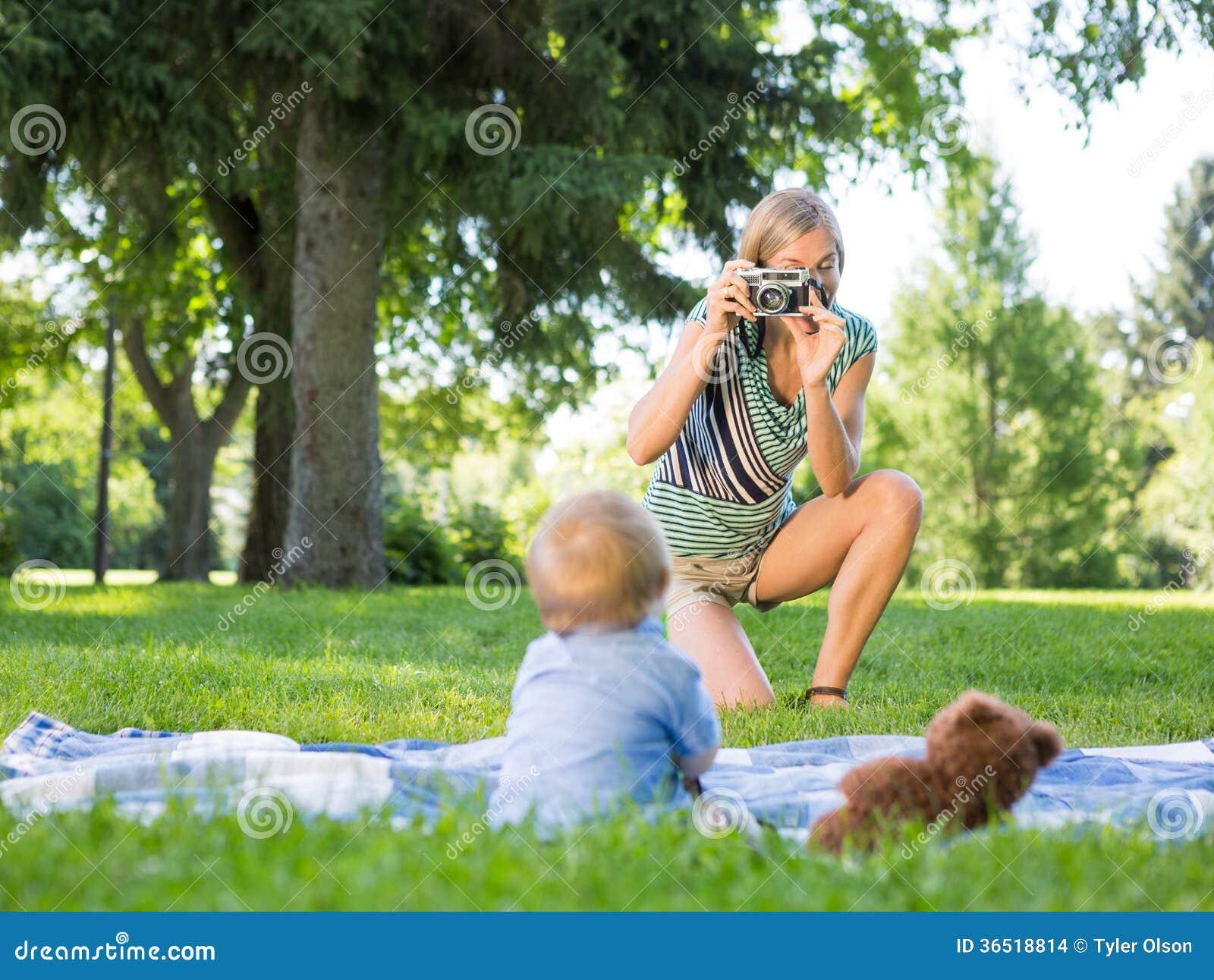 Mère photographiant le bébé garçon au parc