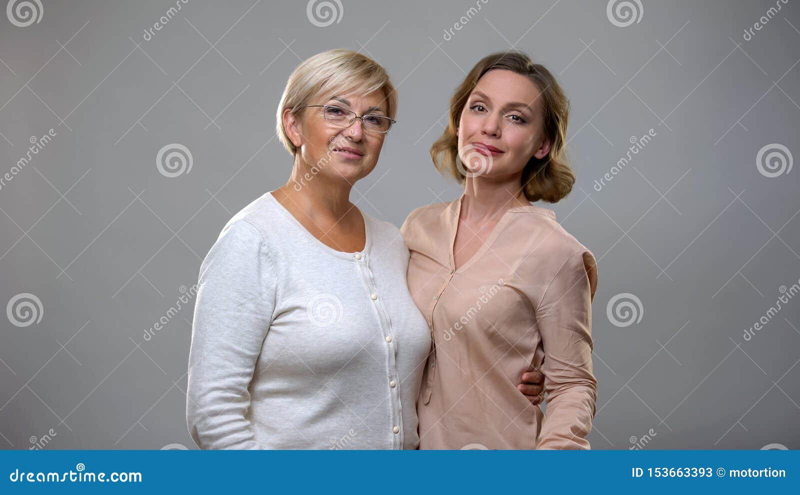 Mère pluse âgé étreignant la jeune femelle sur le fond gris, connexion de famille, amour
