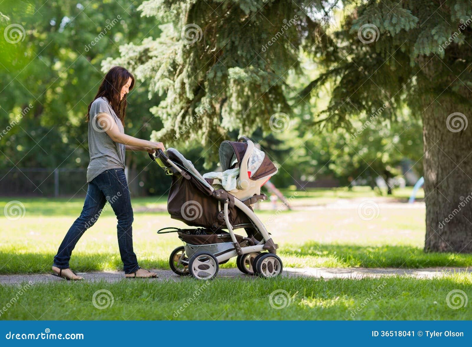 Mère poussant la voiture d enfant en parc