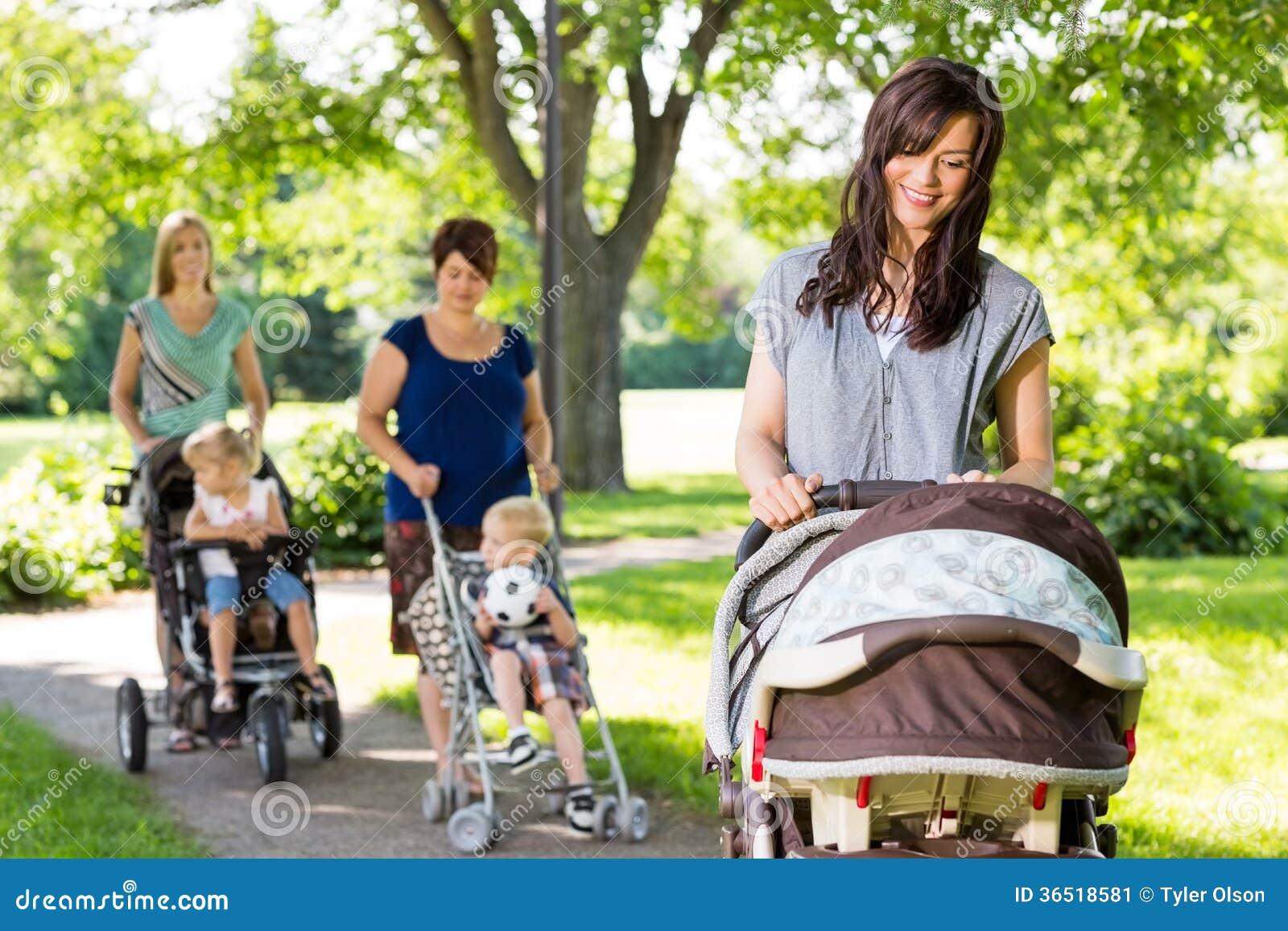 Mère regardant le bébé dans la poussette le parc