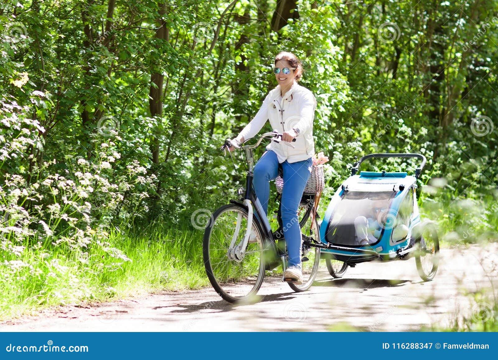 Mère sur la bicyclette avec la remorque de vélo de bébé en parc