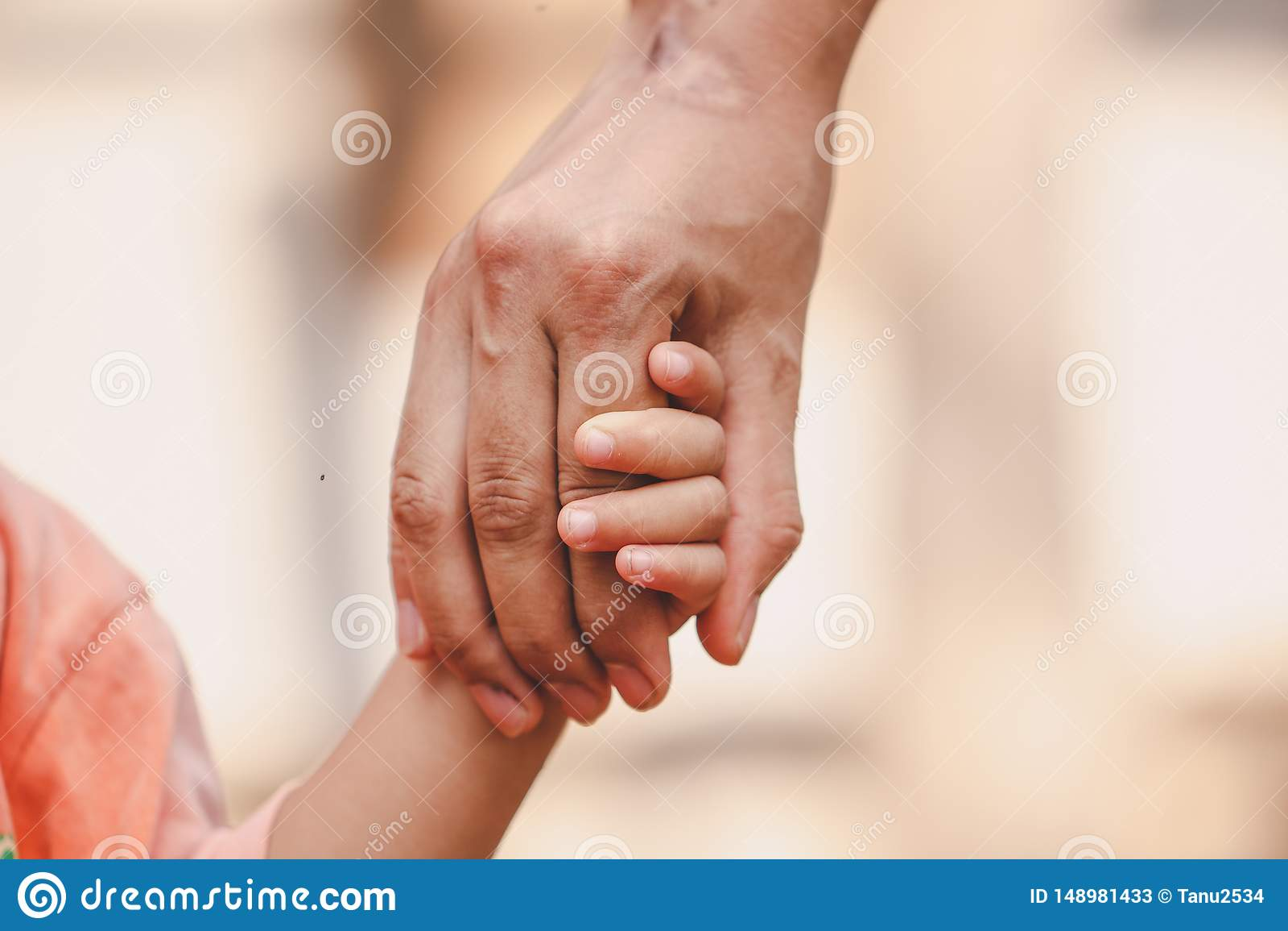 M?re tenant la main d un enfant sur le fond brouill? de bokeh