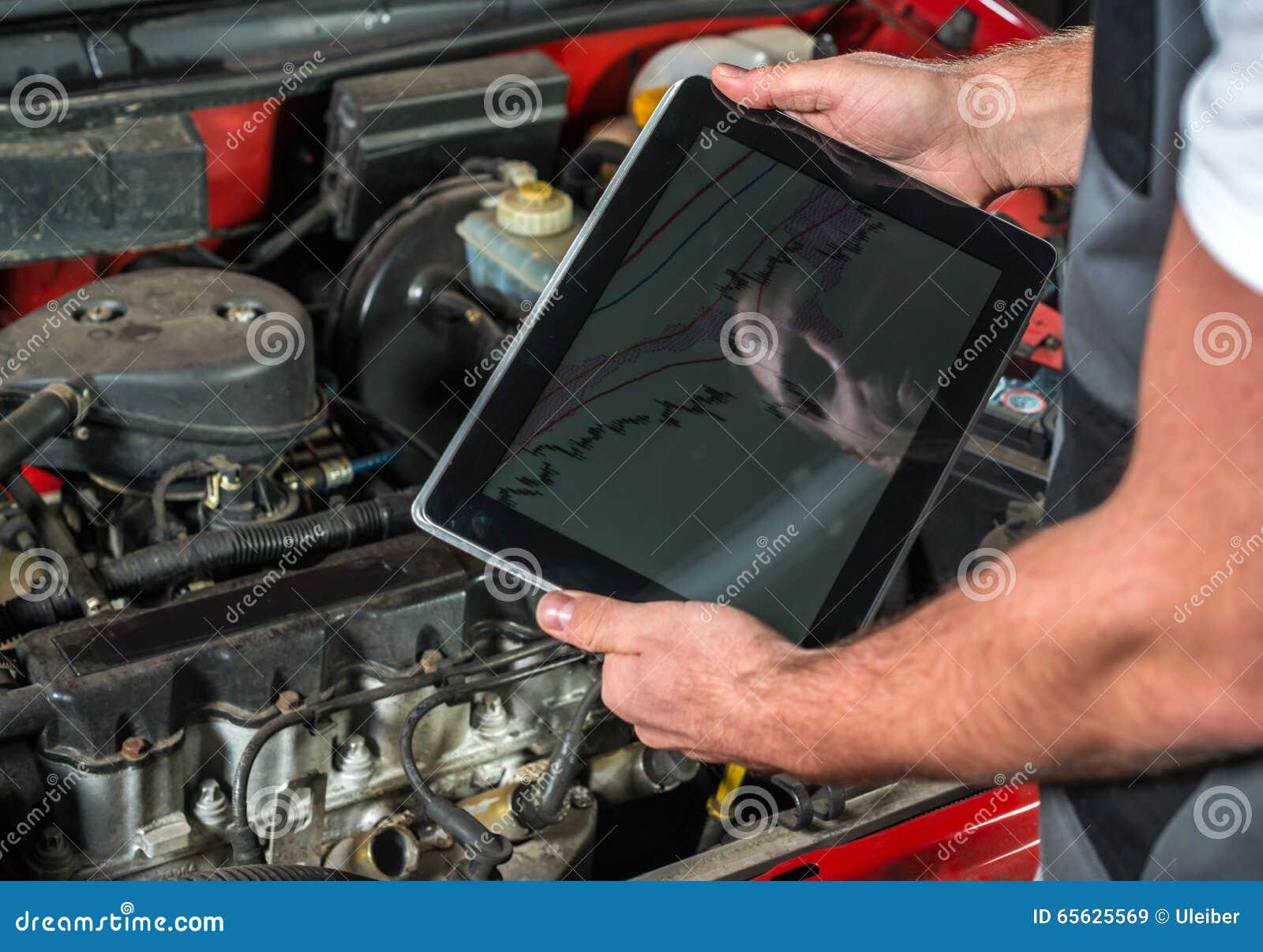 Mécanicien à l aide d un PC de comprimé au garage de réparation
