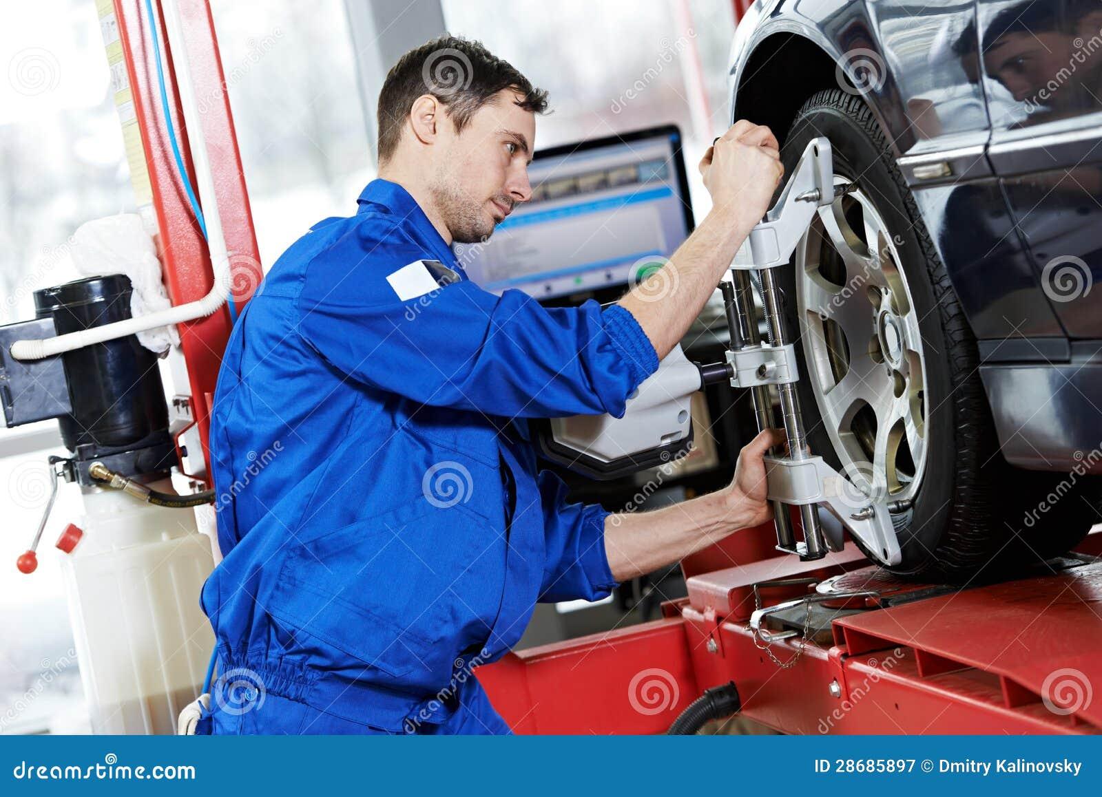 Mécanicien automobile au travail d alignement des roues avec la clé