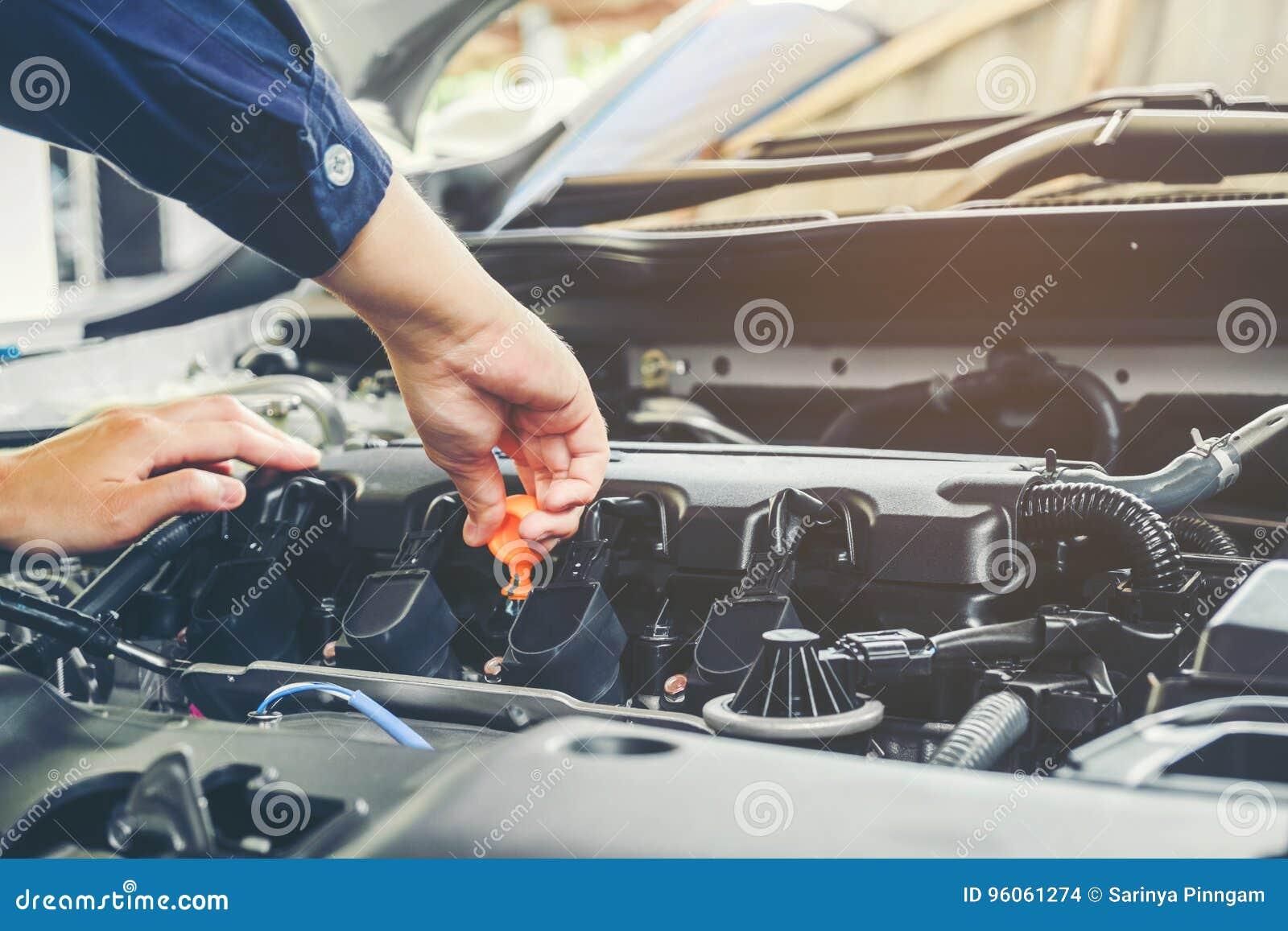 Mécanicien changeant d huile de mécanicien dans le service des réparations automatique