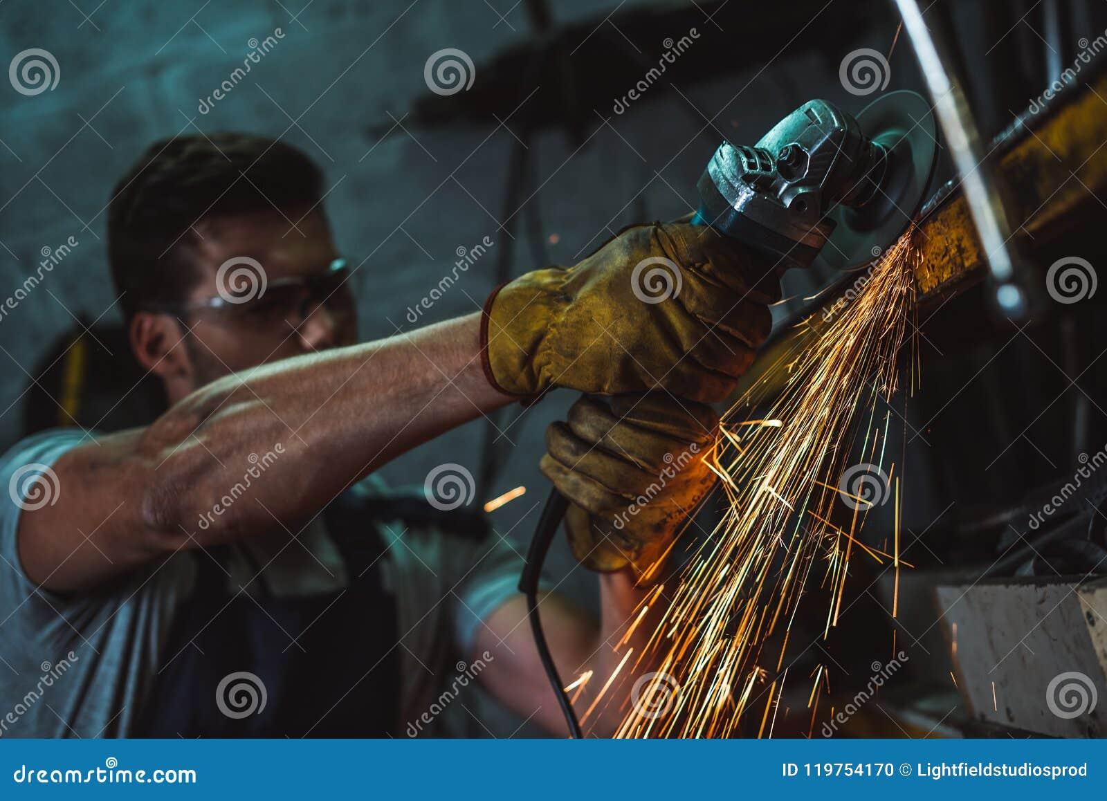 Mécanicien dans les lunettes fonctionnant avec la scie circulaire