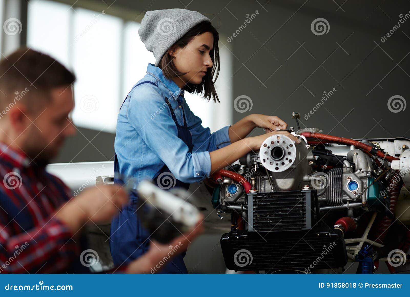 Mécanicien féminin Inspecting Engine dans l atelier