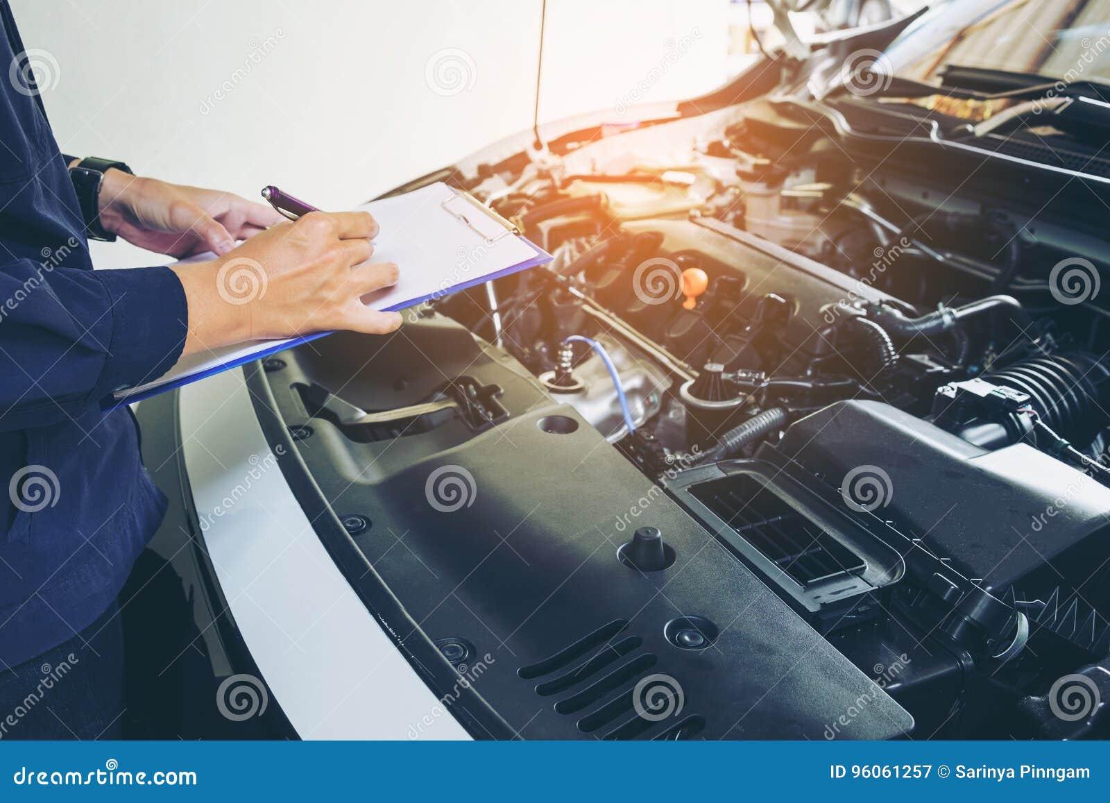 Mécanicien tenant un presse-papiers d ordre de service fonctionnant dans le garage