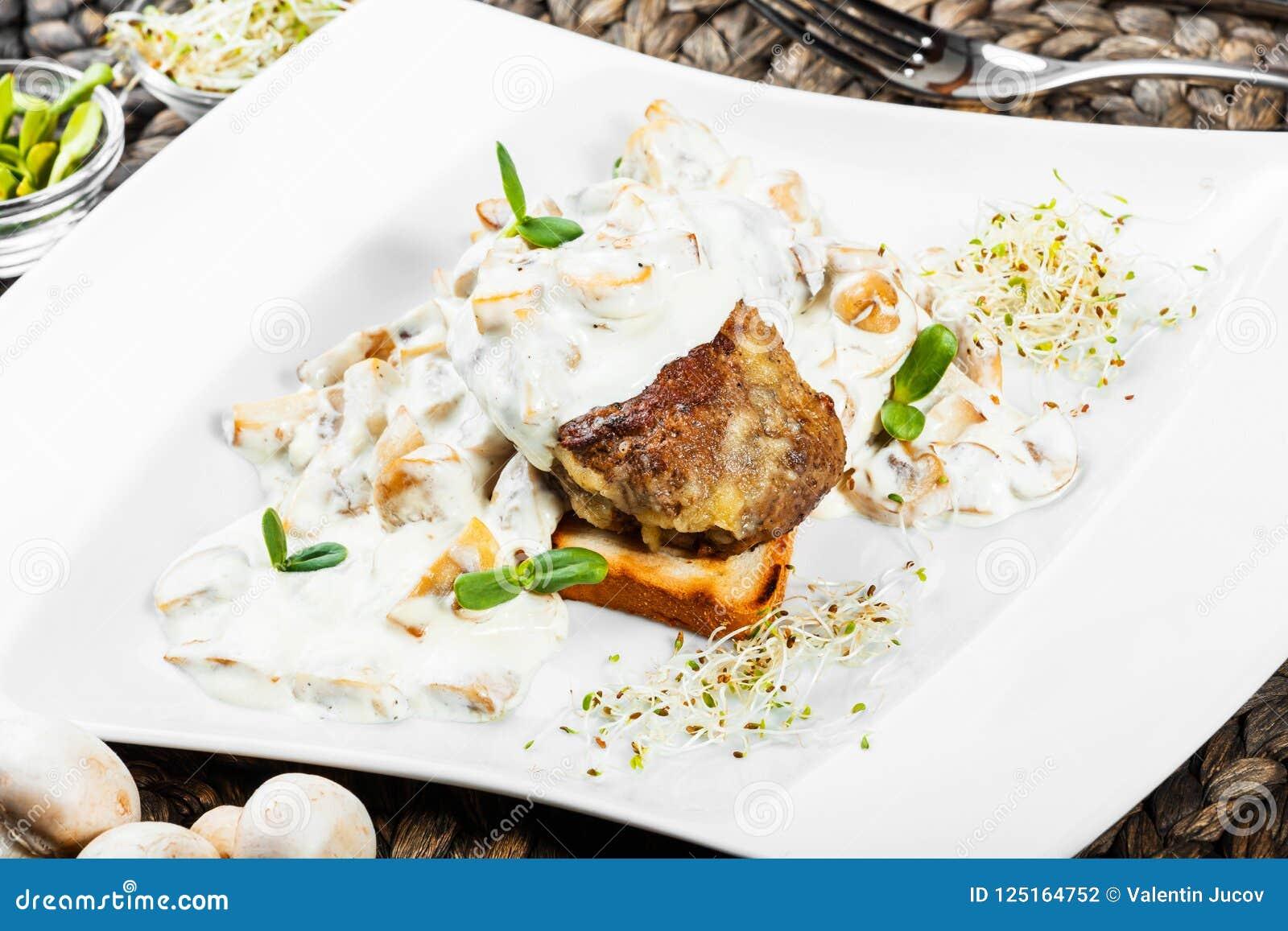 Médaillon grillé de veau de bifteck de viande avec de la sauce au fromage avec des champignons de plat
