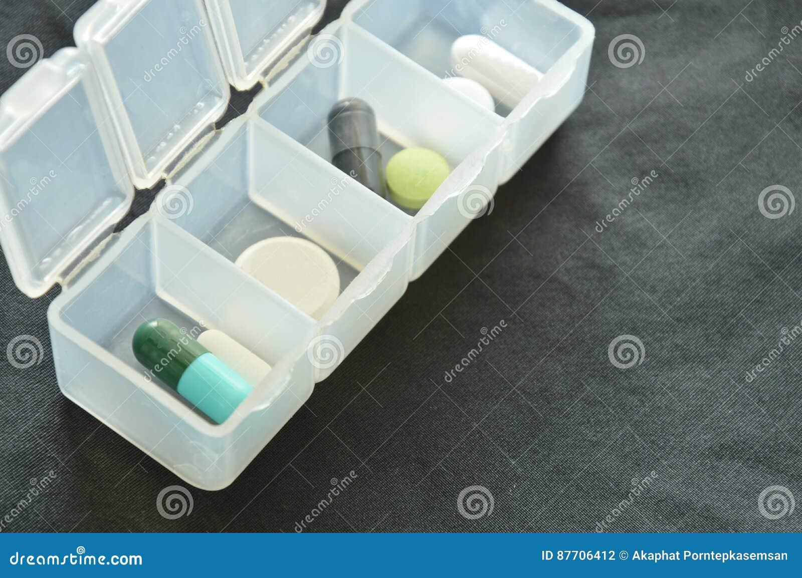Médecine et pilule dans les cartouches en plastique sur le tissu noir