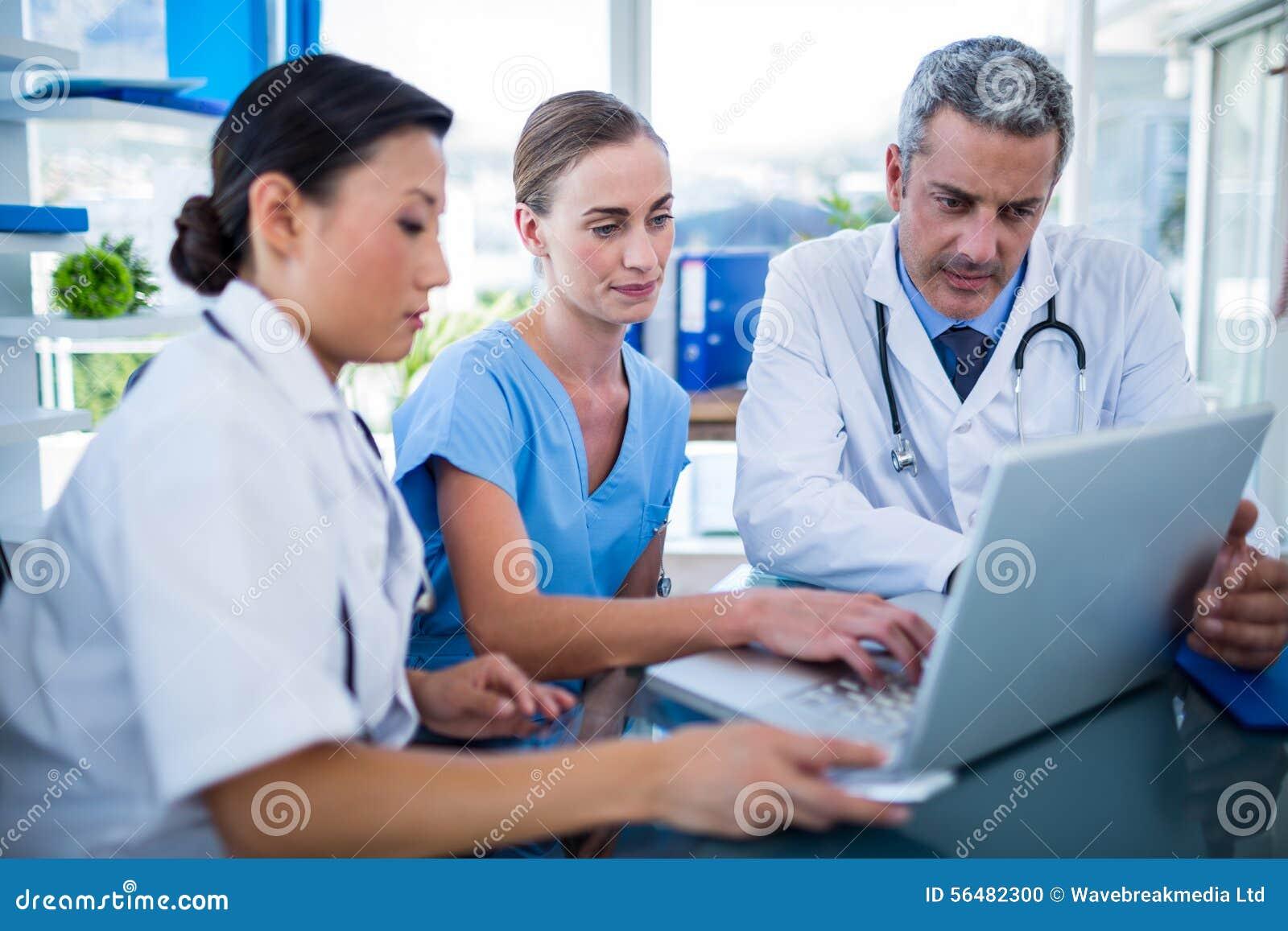 Médecins et infirmière regardant l ordinateur portable
