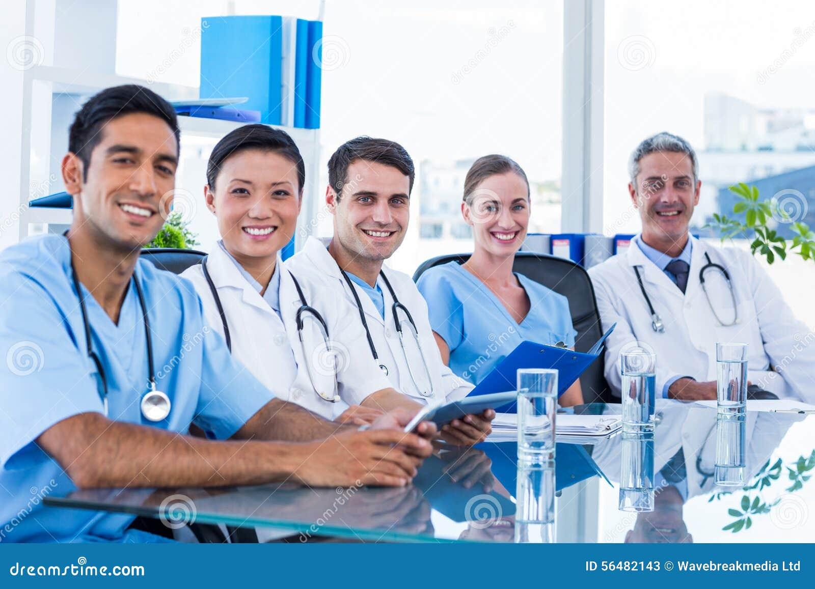 Médecins heureux regardant l appareil-photo tout en se reposant à une table