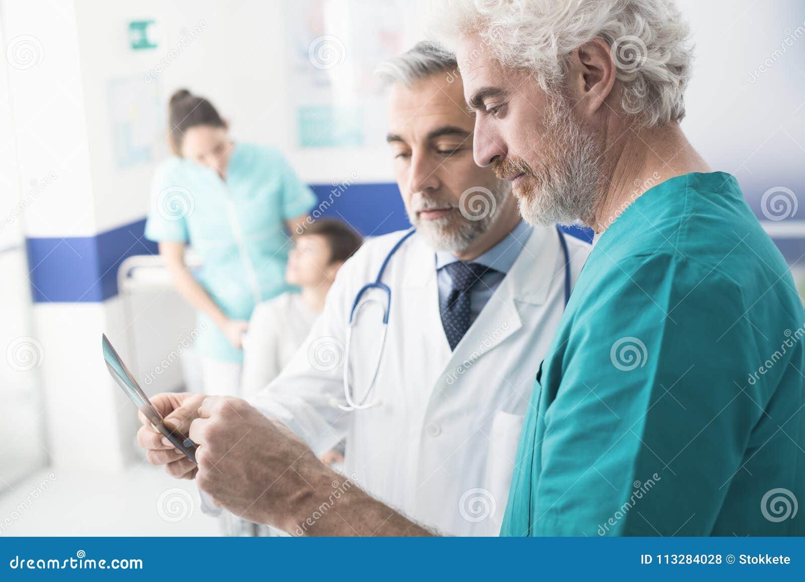 Médecins professionnels examinant le rayon X patient du ` s