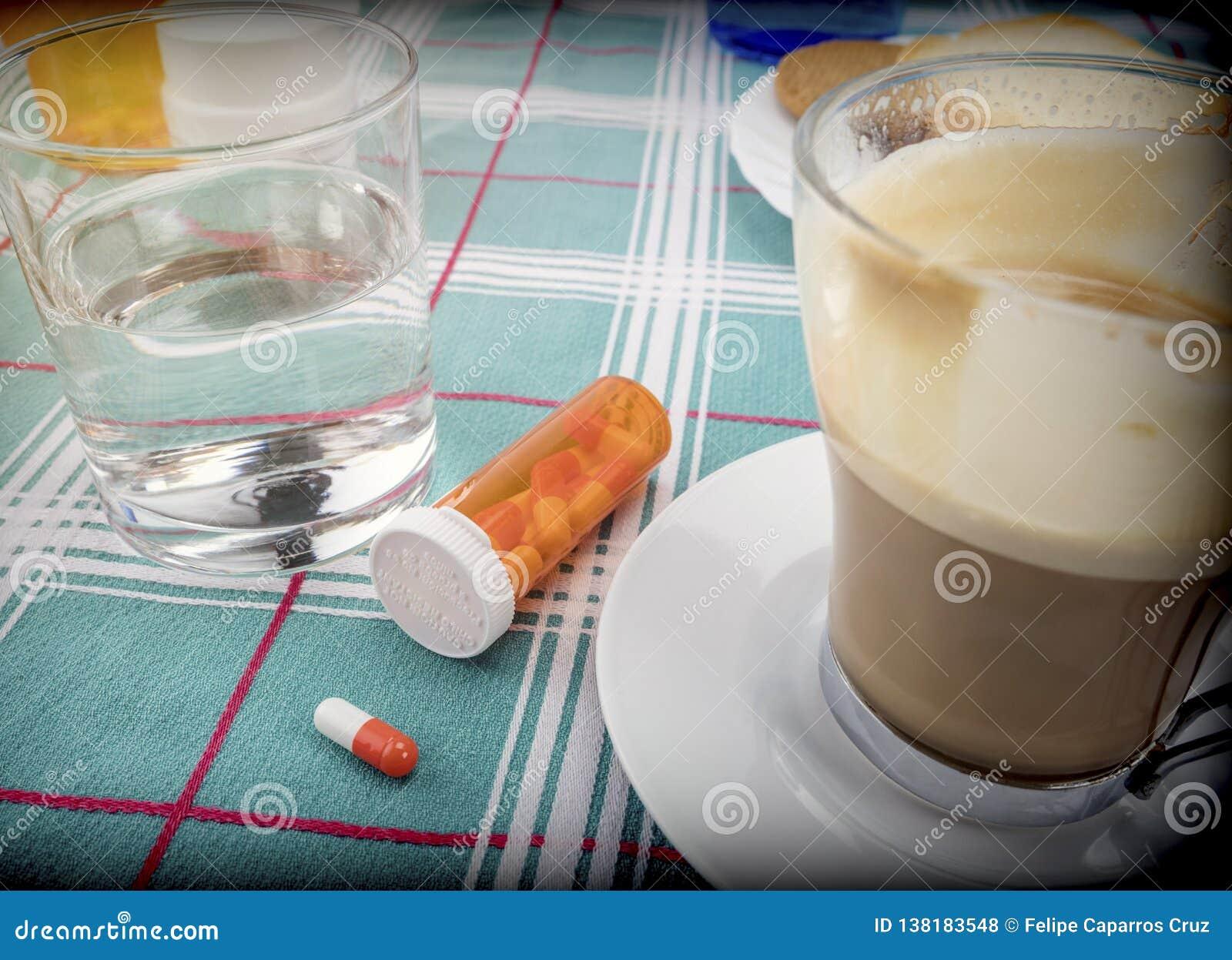 Médicament pendant le petit déjeuner, capsules à côté d un verre de l eau, image conceptuelle