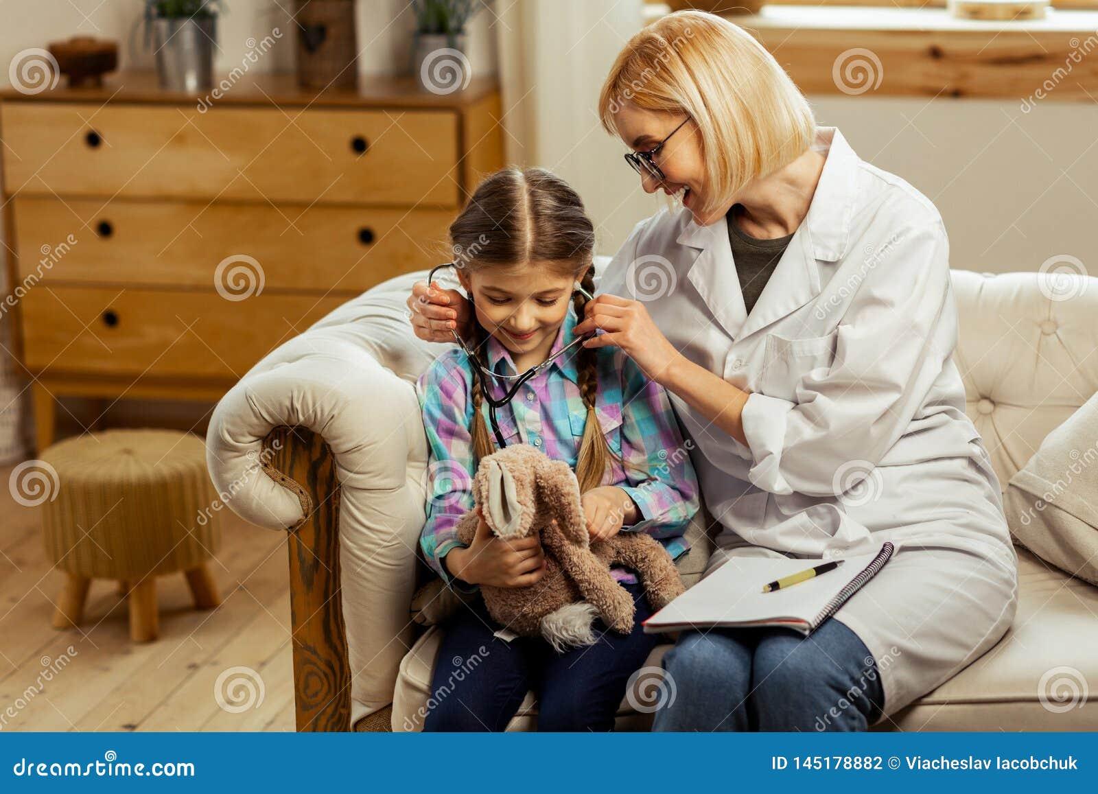 Médico de encantamento que dá um estetoscópio doente da menina para tentar sobre